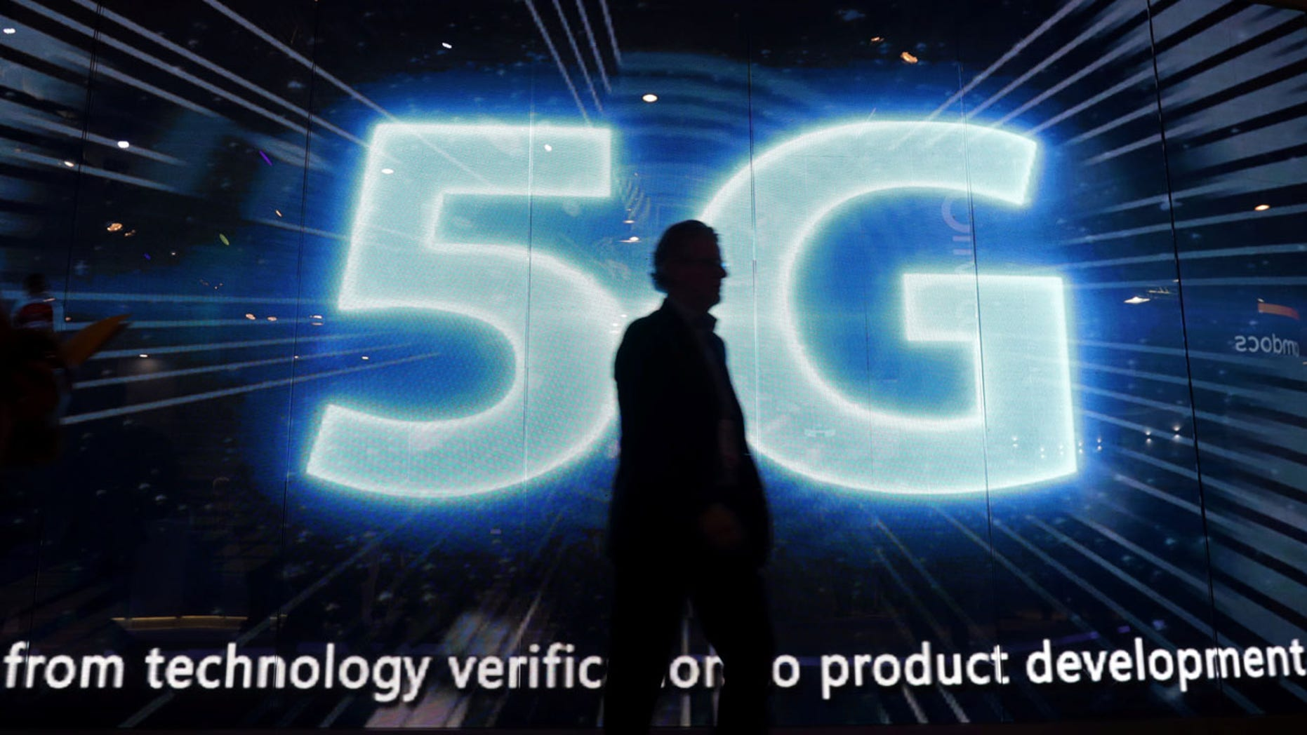 """FILE: A visitors walks past a 5G sign during Mobile World Congress in Barcelona last year. The technology is seen as a """"key area of competition"""" internationally."""