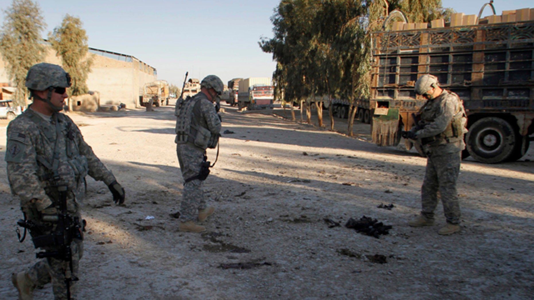 Feb. 7, 2011: U.S. soldiers inspect the scene of an explosion in Kandahar south of Kabul, Afghanistan that killed at least one person and wounded two.