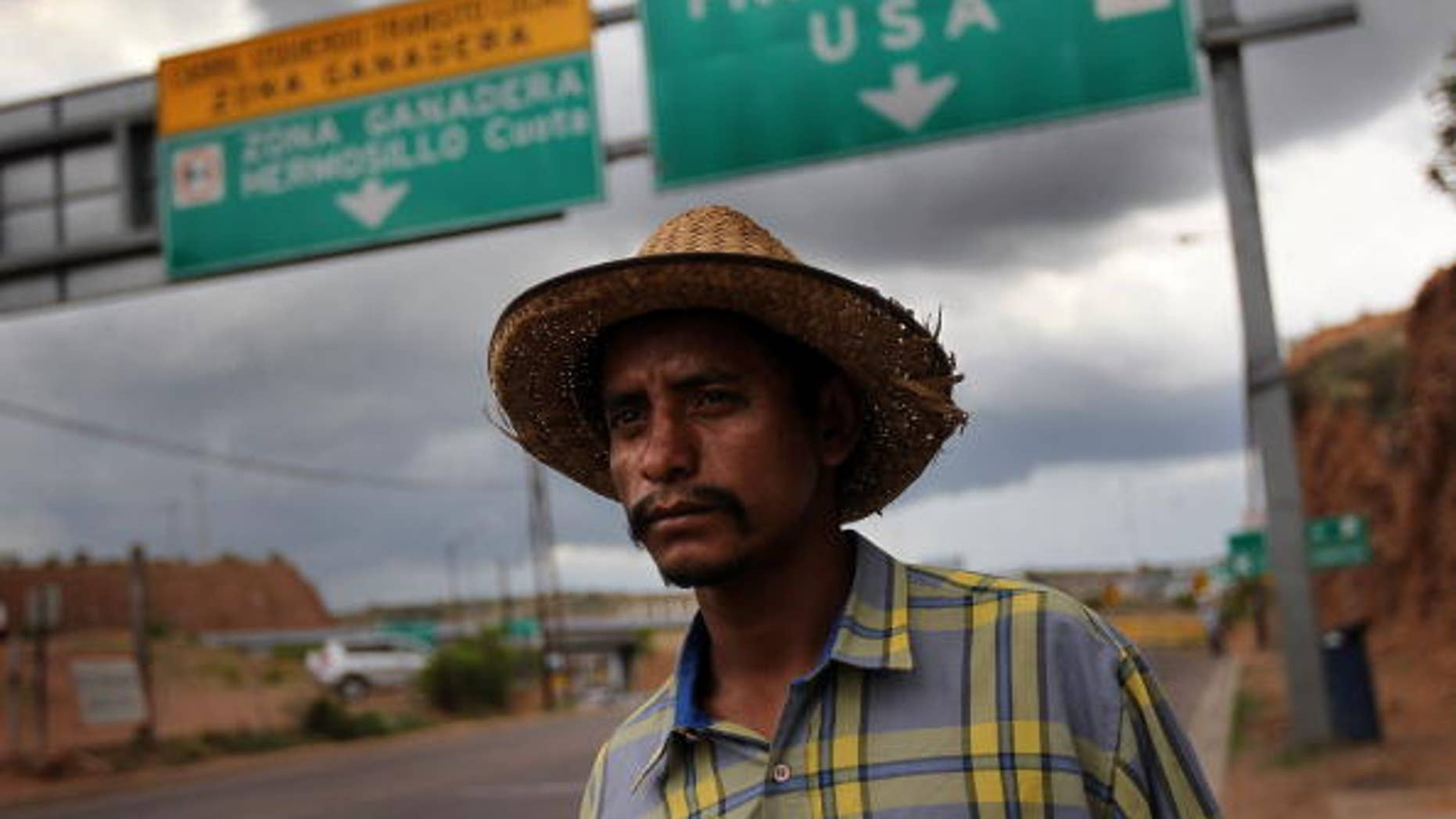Jul 27:   Mexican immigrant Luis Manuel, 29, walks along the U.S.- Mexico border after being deported from Arizona to Nogales, Mexico.