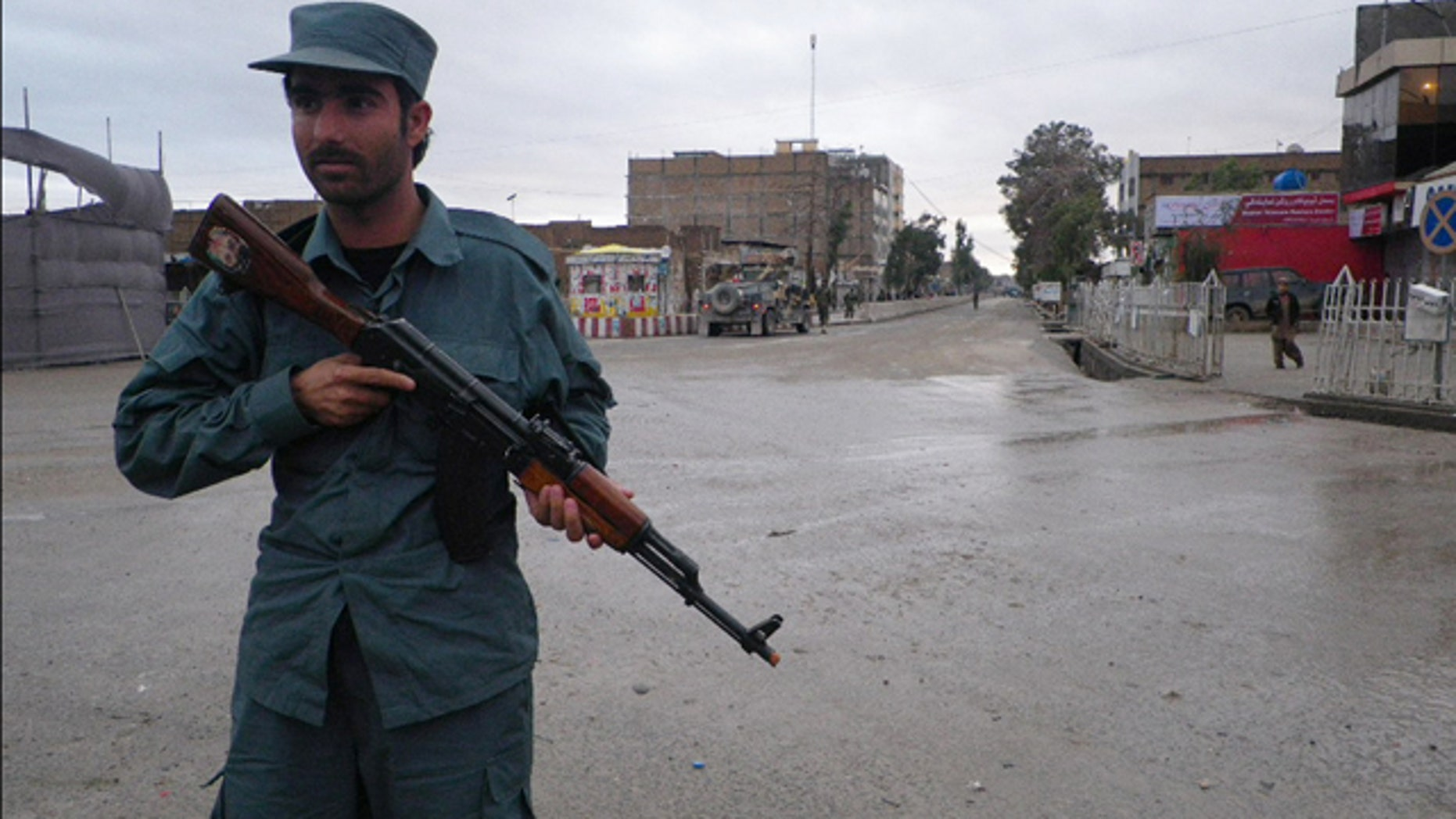 FILE: An Afghan policeman stands guard on the road leading to the Kandahar police headquarters in Kandahar south of Kabul, Afghanistan.