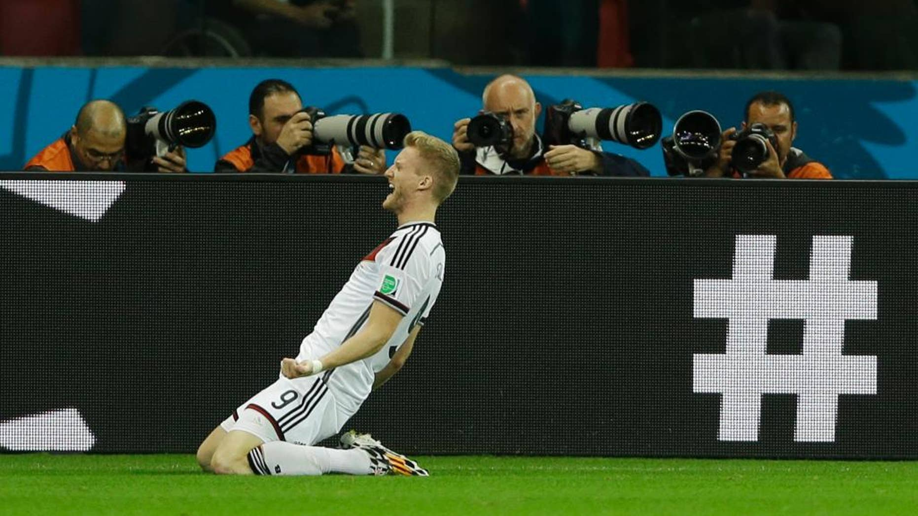 Germany's Andre Schuerrle celebrates after scoring his side's first goal in overtime during the World Cup round of 16 soccer match between Germany and Algeria at the Estadio Beira-Rio in Porto Alegre, Brazil, Monday, June 30, 2014. (AP Photo/Kirsty Wigglesworth)