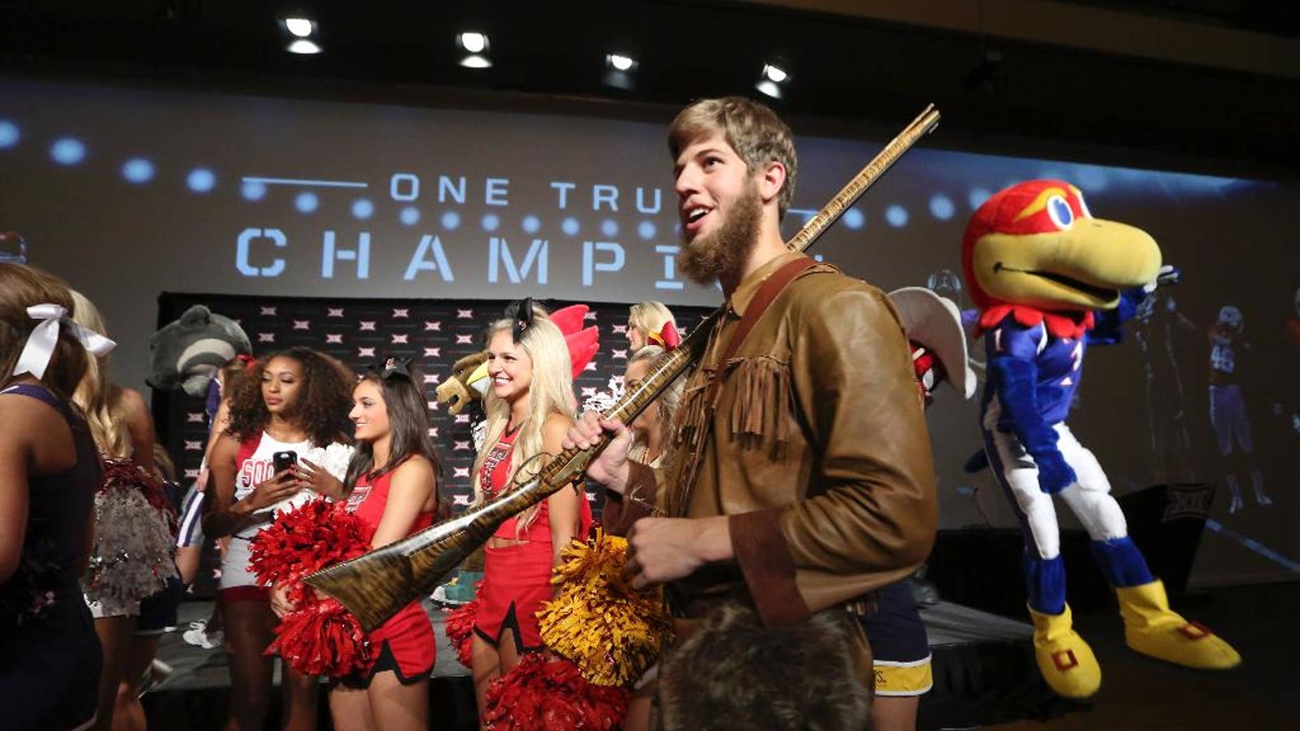 Michael Garcia, dressed as West Virginia's mountaineer mascot, caries a musket after posing for a photo with cheerleaders and mascots at the Big 12 Conference NCAA college football media days in Dallas, Tuesday, July 22, 2014. (AP Photo)