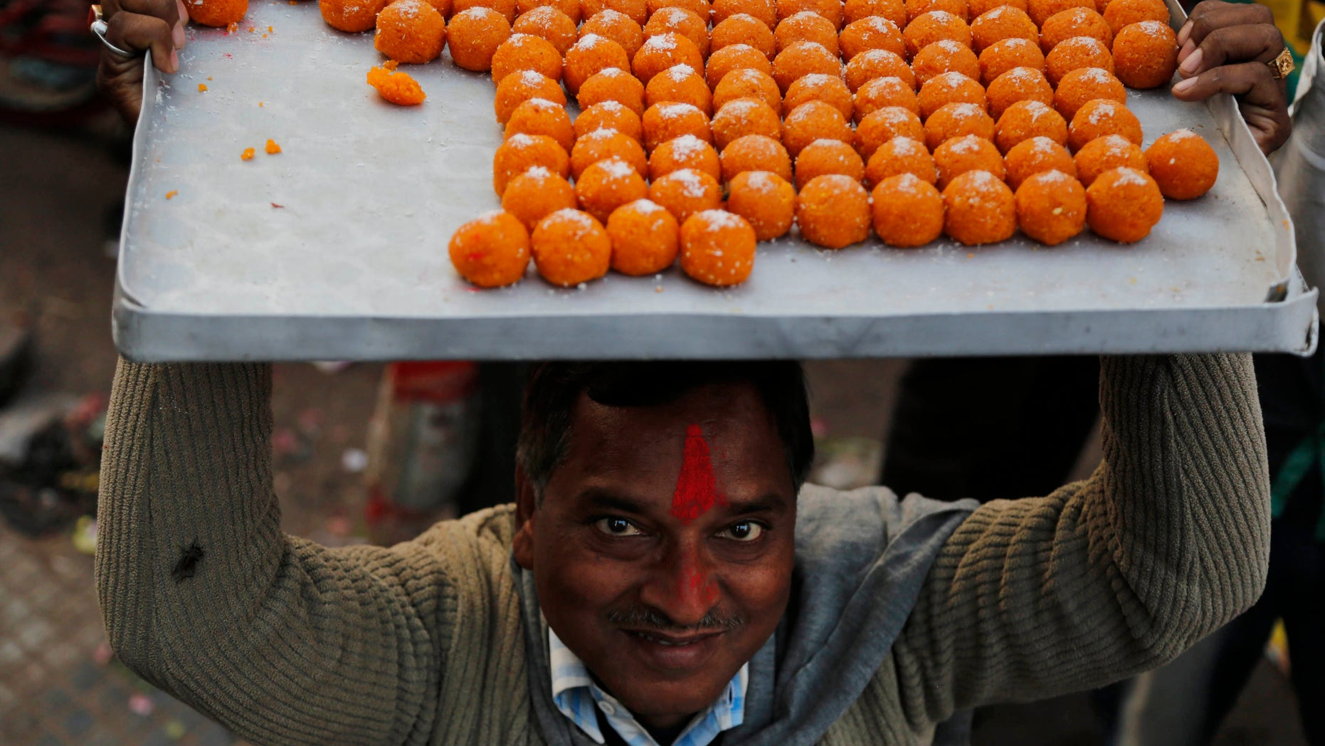 A man carries sweets to distribute as India's main opposition Bharatiya Janata Party (BJP) supporters celebrate the party's victory in various state Assembly elections in Allahabad,India , Sunday, Dec. 8, 2013. BJP, the main Hindu nationalist party, appeared to make strong political gains in four heartland states Sunday, as preliminary results showed the ruling Congress party sidelined in a race seen as a test before next year's general election. (AP Photo/Rajesh Kumar Singh)