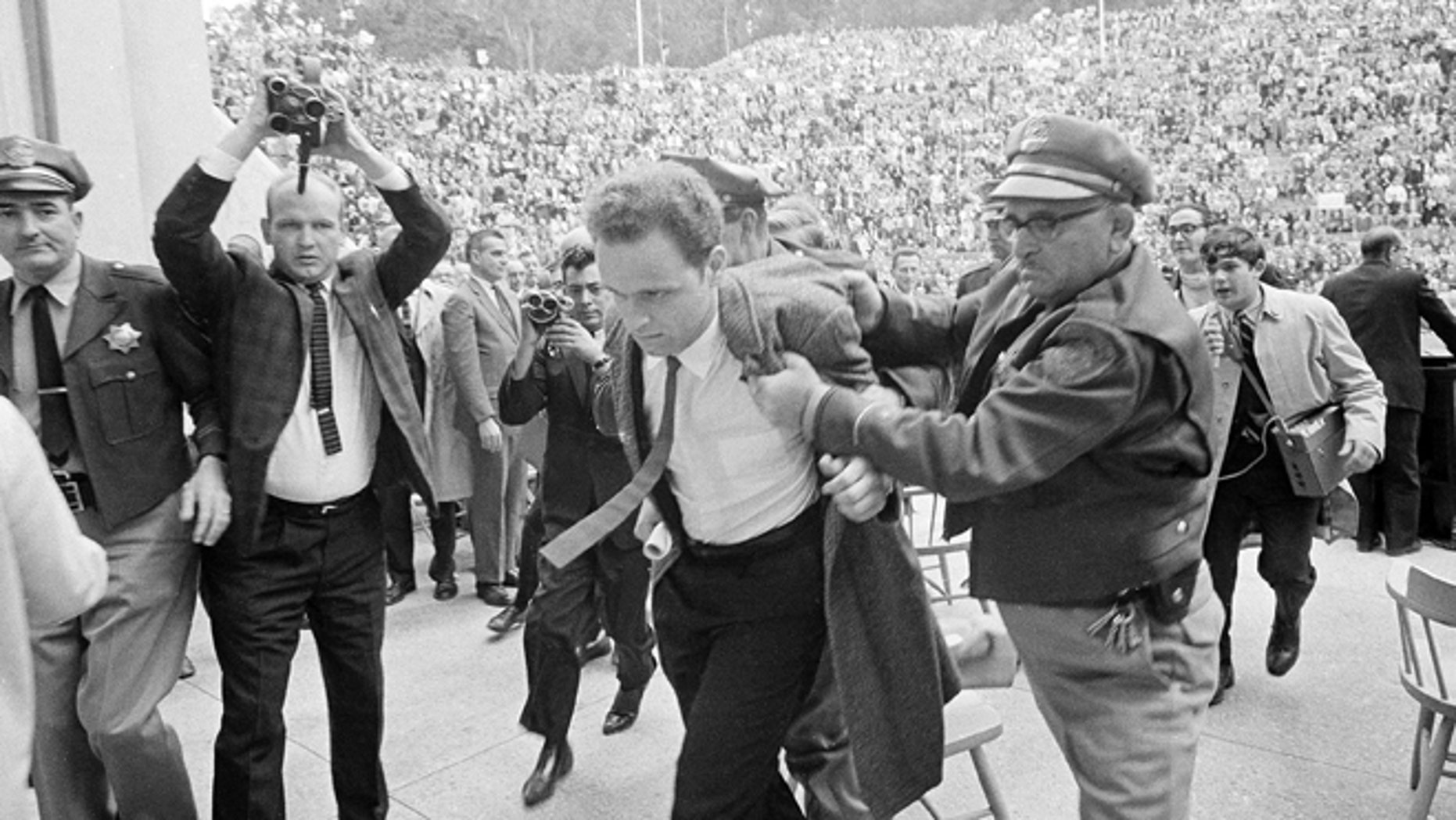 FILE 1964: Mario Savio, leader of the Berkeley Free Speech Movement, is restrained by police as he walks on to the platform at the University of California's Greek Theater in Berkeley, Calif. Savio attempted to speak directly following the appearance of University President Clark Kerr. He was later permitted to make two announcements to the assembled students.