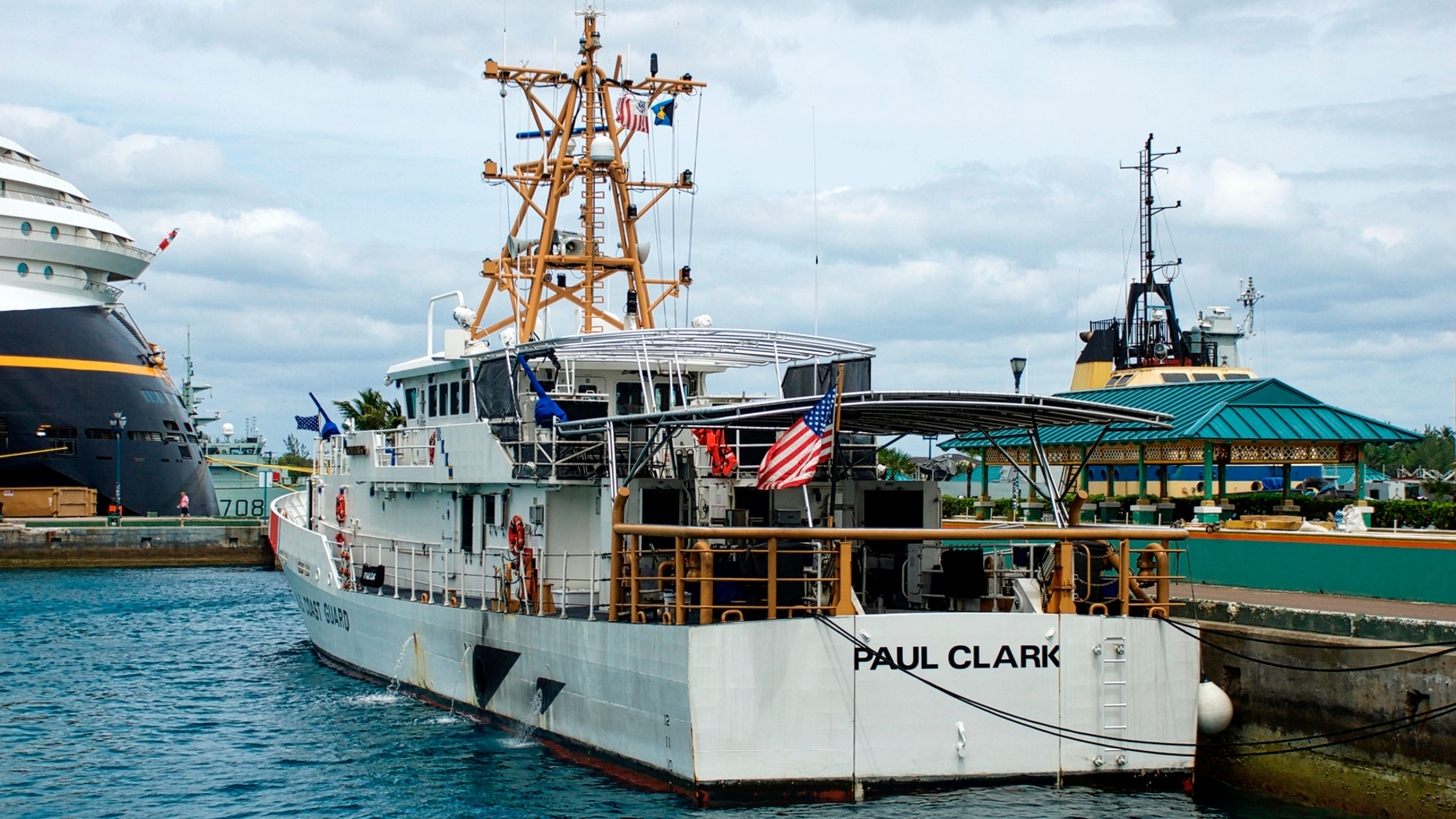 """The U.S. Coast Guard ship """"Paul Clark"""" sits dockside at port in Nassau, The Bahamas, as the stern of the Disney Dream passenger cruise ship."""