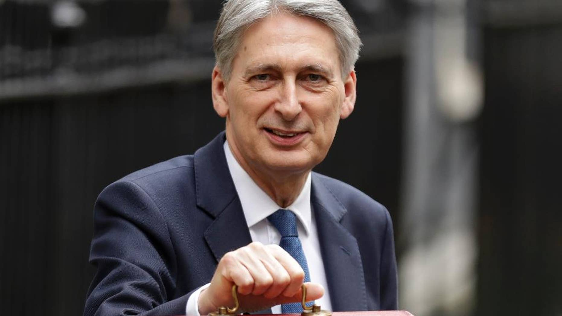 FILE - In this Wednesday, March 8, 2017 file photo, Britain's Chancellor of the Exchequer Philip Hammond poses for the media with his traditional red dispatch box before delivering his annual budget speech to Parliament in London. Britain's Treasury chief has told lawmakers in his Conservative Party on Wednesday, March 15 that the government will not go ahead with plans for higher taxes on self-employed workers after the plans touched off outrage from within the Tory ranks. Philip Hammond announced an increase in National Insurance contributions for the self-employed in his budget last week. (AP Photo/Matt Dunham, file)