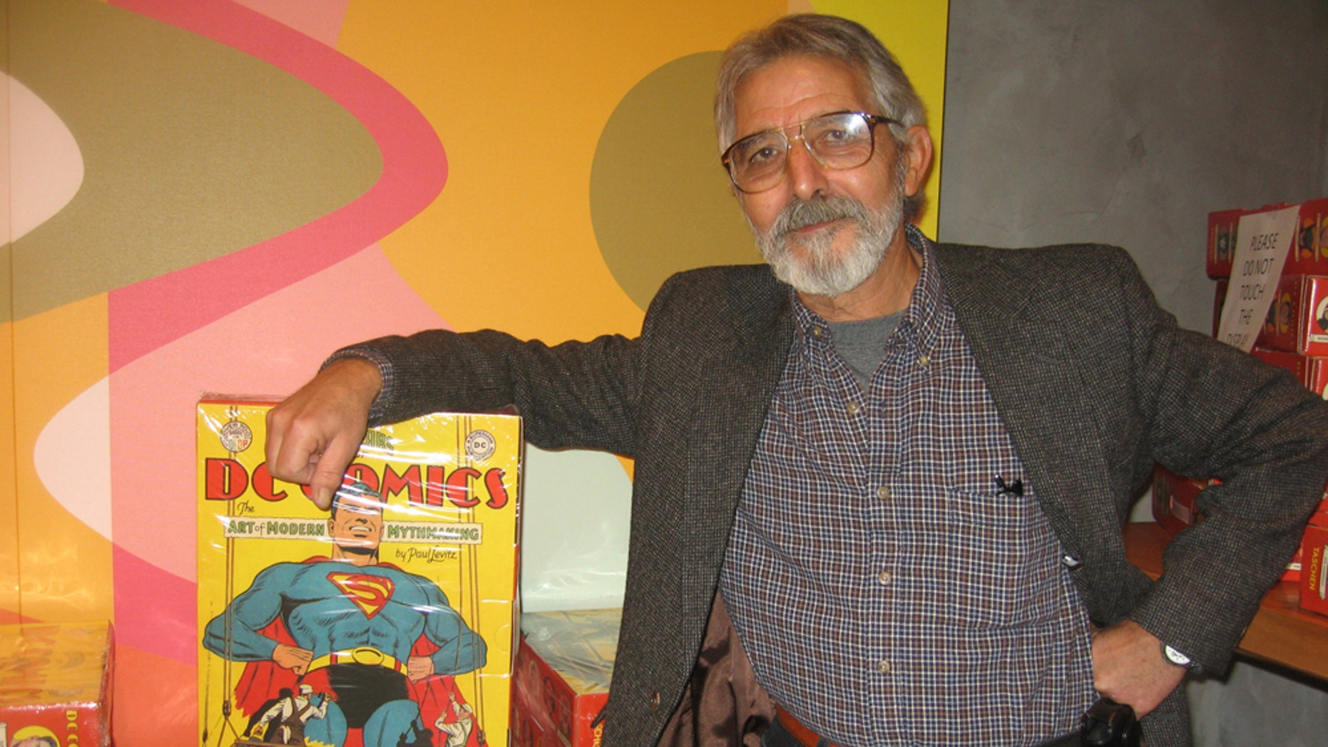 "Comic book artist José Luís García-López with the supersized, Eisner-winning ""75 Years of DC Comics: The Art of Modern Mythmaking"""