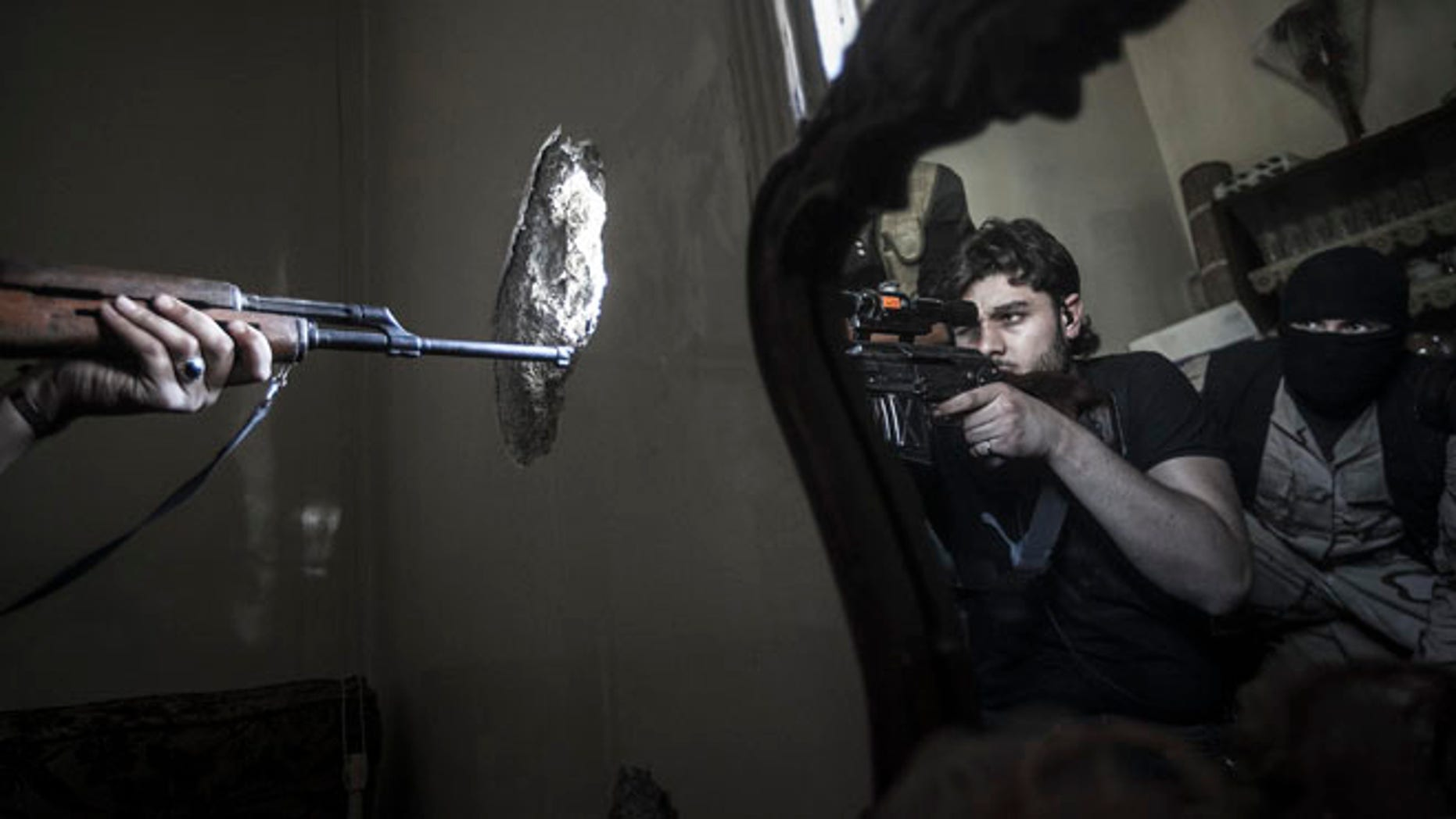 FILE 2012: A rebel sniper aims at a Syrian army position, seen with another rebel fighter reflected in a mirror, in a residential building in the Jedida district of Aleppo, Syria.