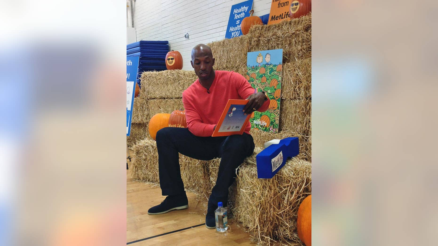 """Retired NBA basketball player Chauncey Billups reads """"It's the Great Pumpkin, Charlie Brown"""" to students at Fairview Elementary in Denver on Monday, Oct. 27, 2014. The NBA season is about to tip off and for the first time in nearly two decades, Billups won't be taking the court. (AP Photo/Pat Graham)"""