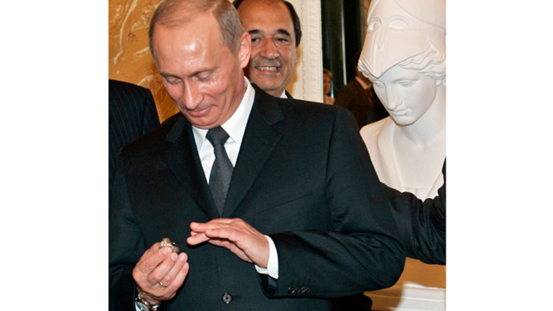 FILE - In this June 25, 2005, file photo, Russian President Vladimir Putin holds a diamond-encrusted 2005 Super Bowl ring belonging to New England Patriots NFL football team owner Robert Kraft during a meeting of American business executives at the 18th century Konstantin Palace outside St. Petersburg, Russia. When Putin arrived in London on Sunday, June 16, 2013, his spokesman was asked about a New York Post story quoting Kraft saying Putin pocketed his Super Bowl ring in 2005. Putin said hes happy to buy New England Patriots owner Robert Kraft another ring, but its absurd to suggest he stole the Super Bowl one. (AP Photo/Alexander Zemlianichenko, File)