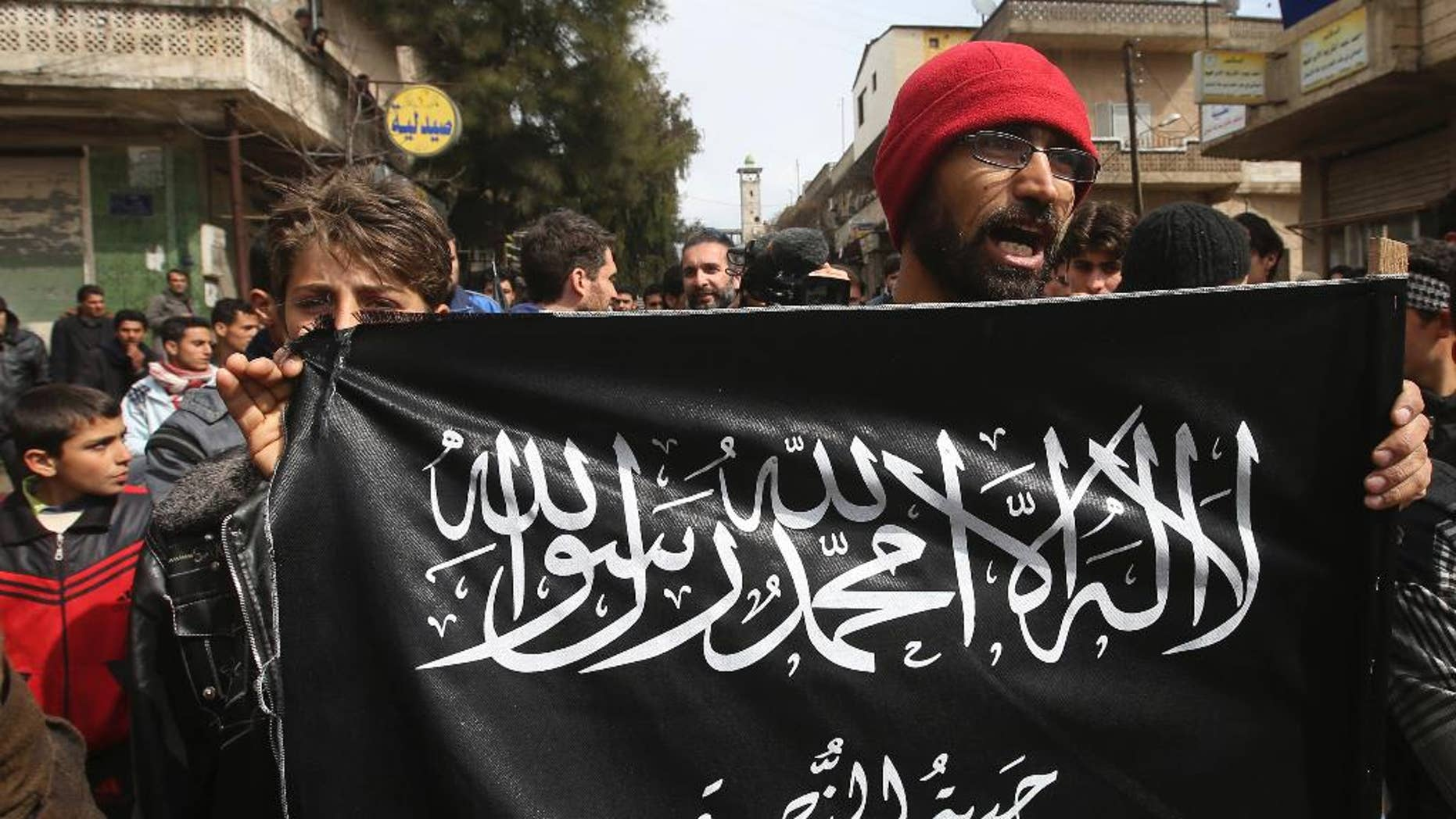 FILE- In this March 1, 2013 file photo, anti-Syrian President Bashar Assad protesters hold the Jabhat al-Nusra flag, as they shout slogans during a demonstration, at Kafranbel town, in Idlib province, northern Syria.
