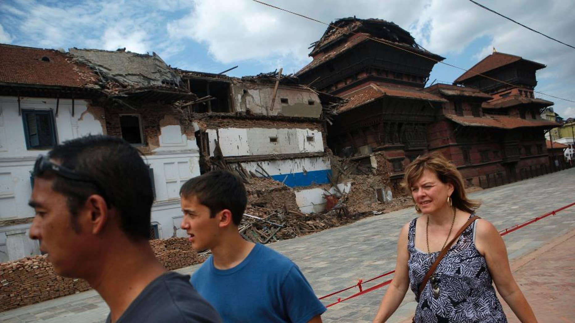 FILE- In this June 15, 2015 file photo, tourists walk near damaged buildings at Basantapur Durbar Square in Kathmandu, Nepal. Nepal's government is urging other countries to lift travel advisories that discourage their citizens from visiting the Himalayan nation following a devastating earthquake in April that killed thousands of people, a government minister said Wednesday, July 15, 2015. (AP Photo/Niranjan Shrestha, file)
