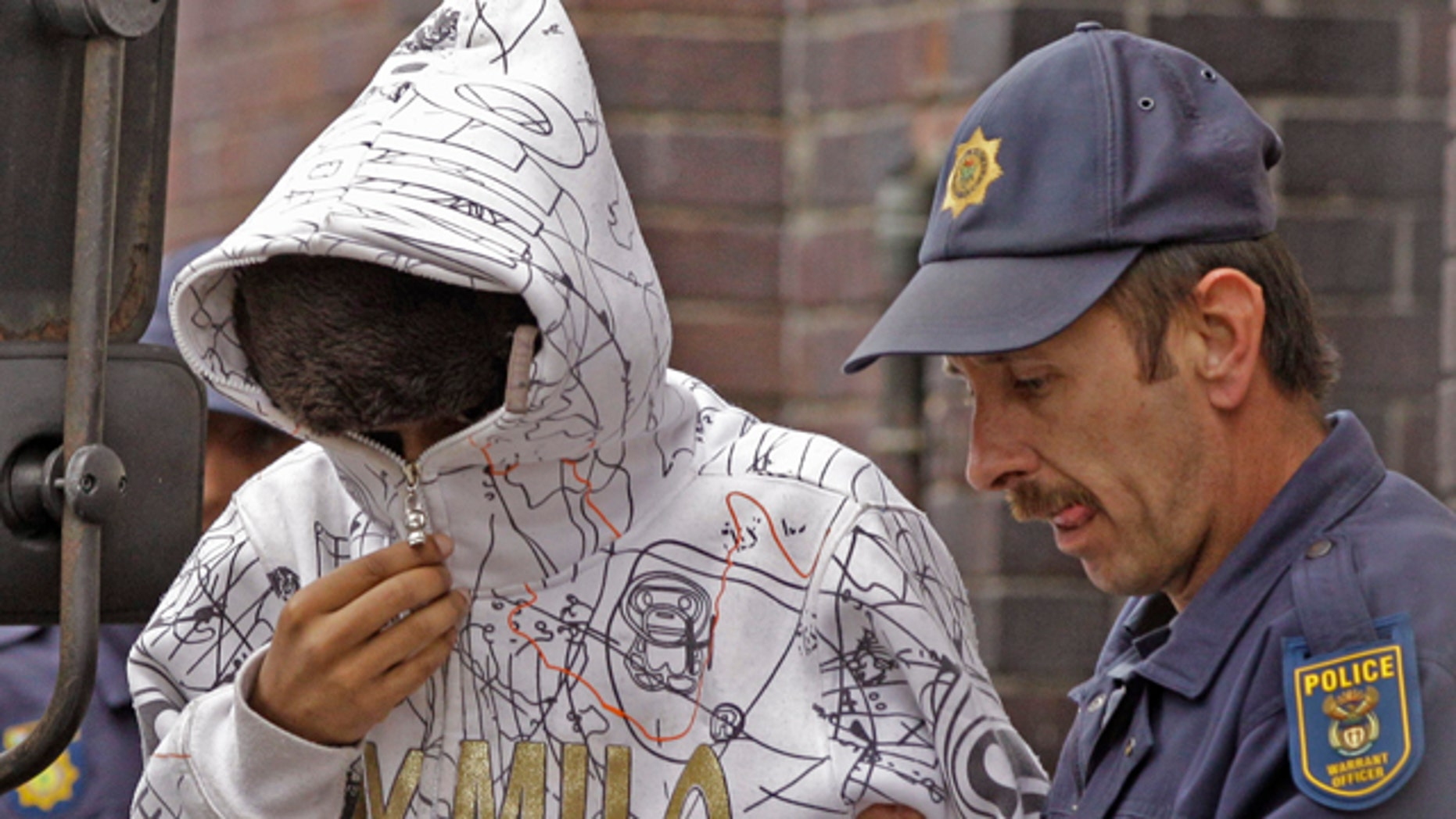 South African Xolile Mngeni, left, accused of taking part in the shooting death of Swedish Anni Dewani is led out of the court building by a police man at Cape Town, South Africa, Tuesday, Sept 20, 2011. Two South Africans allegedly hired by a British newlywed to kill his Swedish bride on their honeymoon in Cape Town will have their case heard by a higher court, a judge ruled Tuesday. At a brief hearing at a magistrate's court, Mziwamadoda Qwabe, 25, and Xolile Mngeni, 23 were ordered to appear before the High Court on Feb. 10. (AP Photo/Schalk van Zuydam)