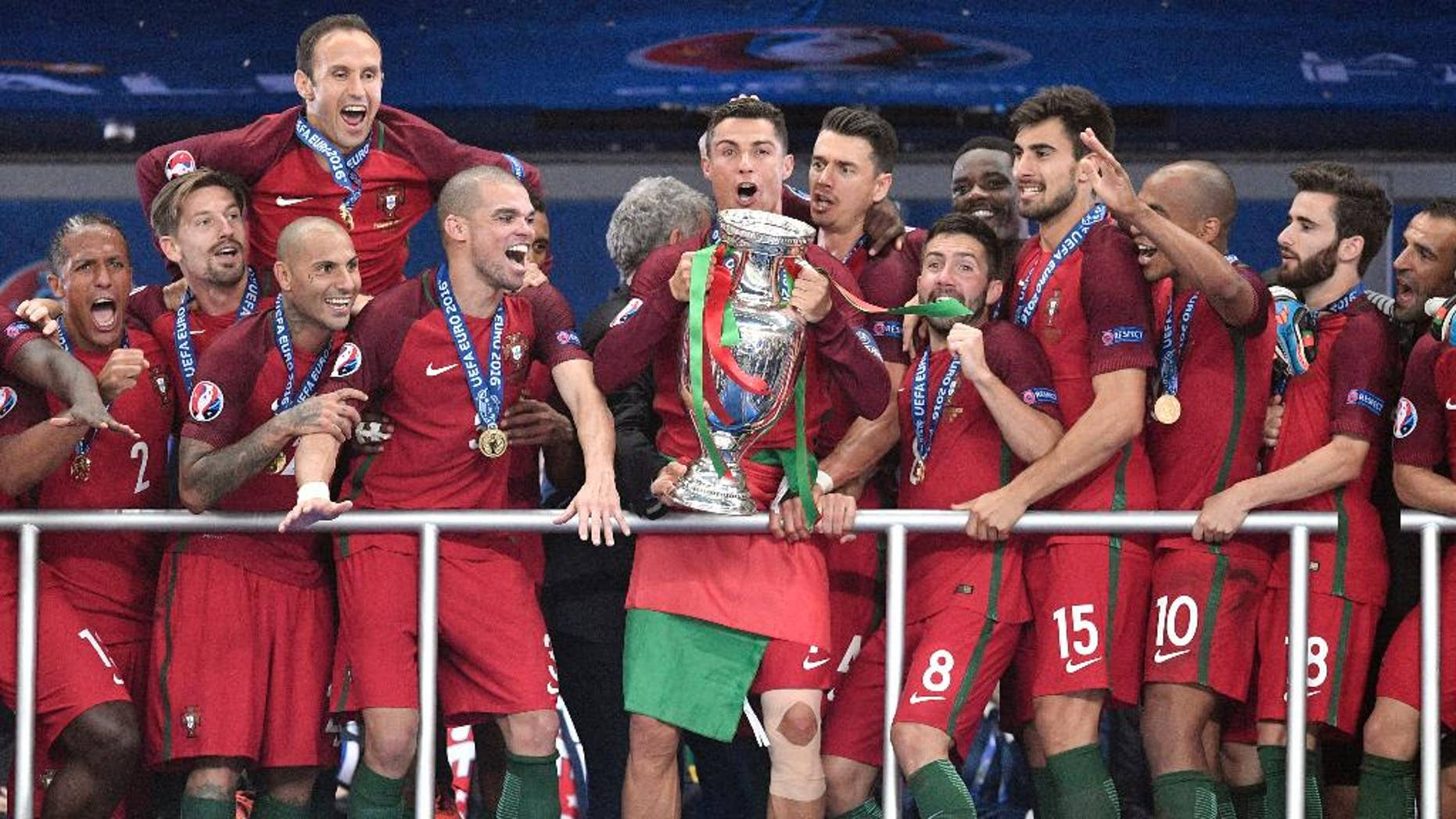 Portugal's Cristiano Ronaldo holds the trophy  after winning the Euro 2016 final soccer match between Portugal and France at the Stade de France in Saint-Denis, north of Paris, Sunday, July 10, 2016. (AP Photo/Martin Meissner)