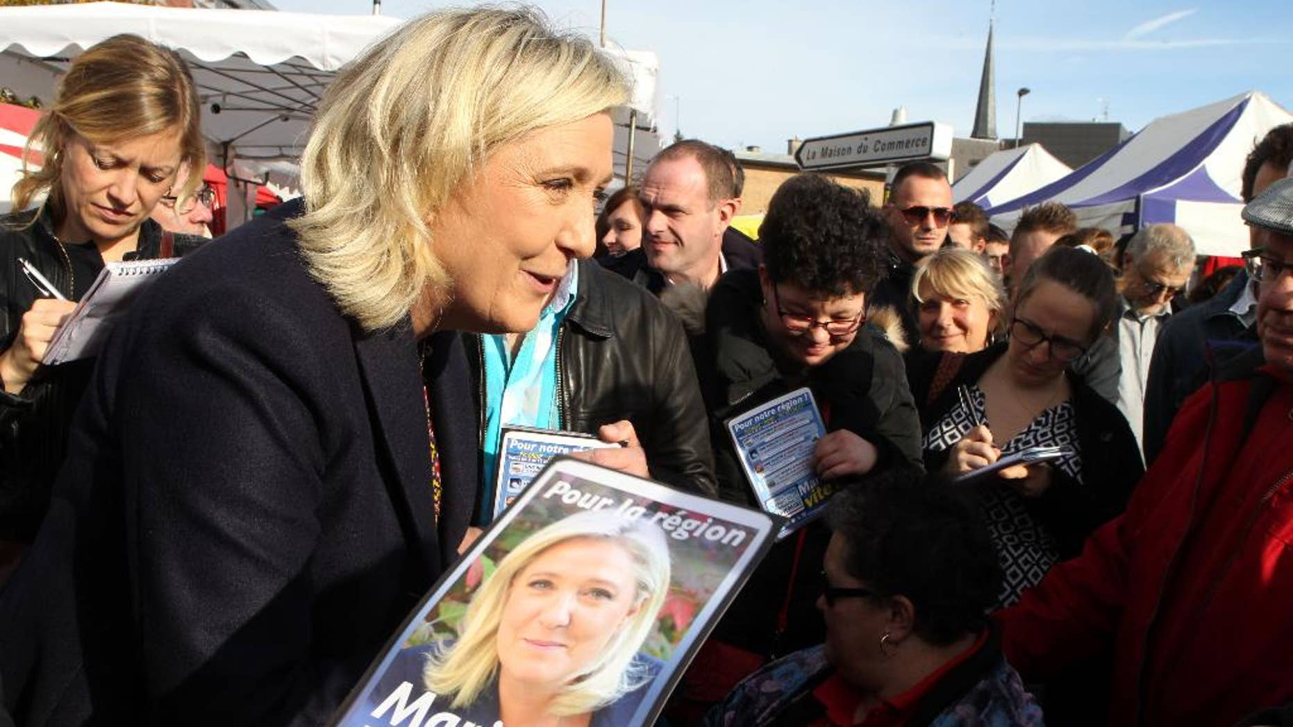 French far-right party leader Marine Le Pen meets residents in a marketplace, in Douai, northern France, as part of the municipal campaign, Saturday, Nov. 7, 2015. Regional elections are taking place next month in which the far right National Front is hoping to increase its political power, in part by capitalizing on tensions over waves of migrants in Europe this year. The first round of the regional elections will take place on Dec. 6, 2015. (AP Photo/Michel Spingler)