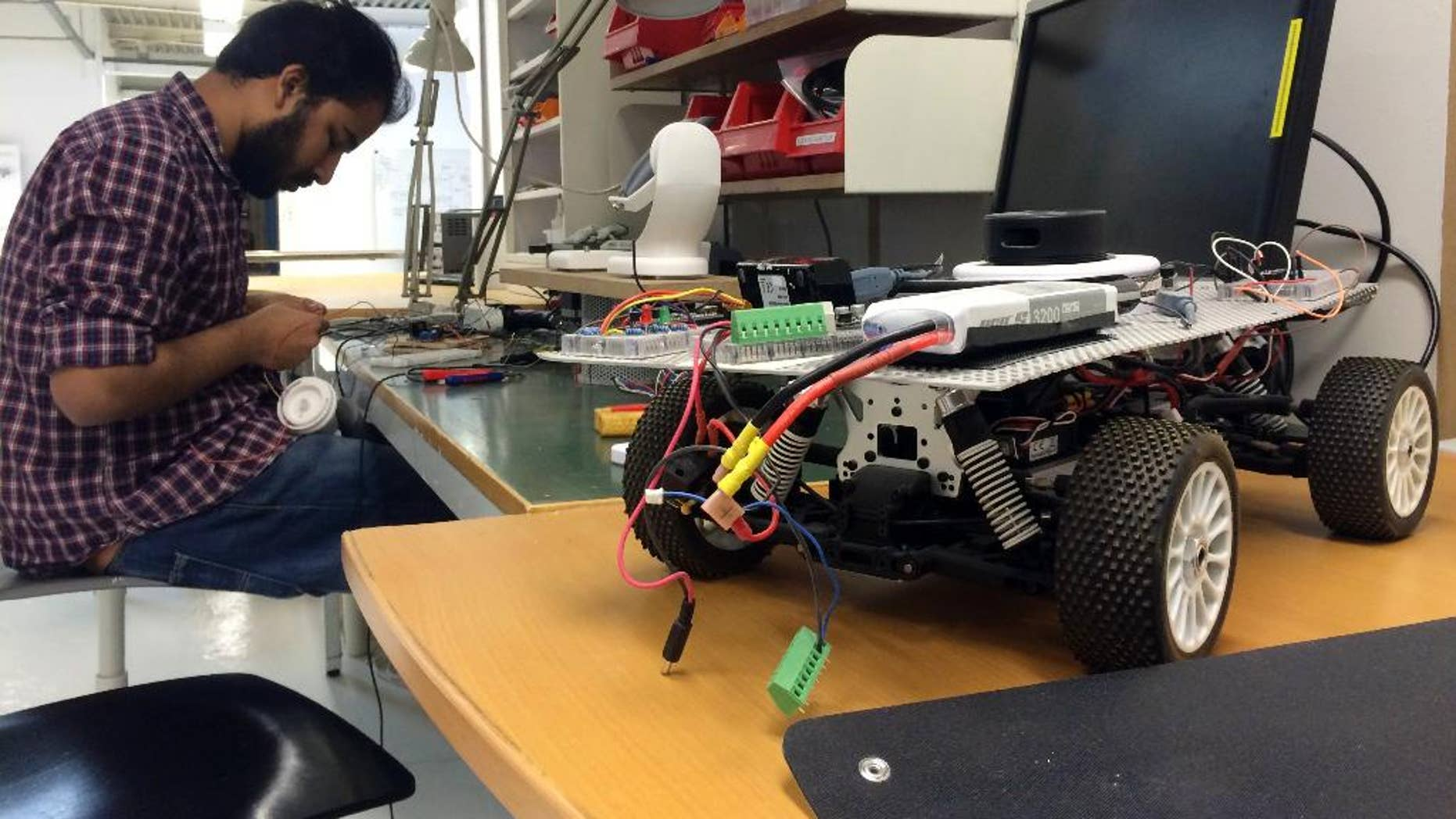 In this Monday, March 13, 2017 photo, a Uniti employee works on prototype steering controls, at the startup's temporary production facility in Lund, Sweden. A group of Swedish students that raised 1.2 million euros in crowdfunding for their startup to build electric cars has caught the attention of German industrial heavyweight Siemens. The two sides said Wednesday that they were starting a partnership that will see them create 50,000 lightweight city cars a year starting next year. (AP Photo/James Brooks)