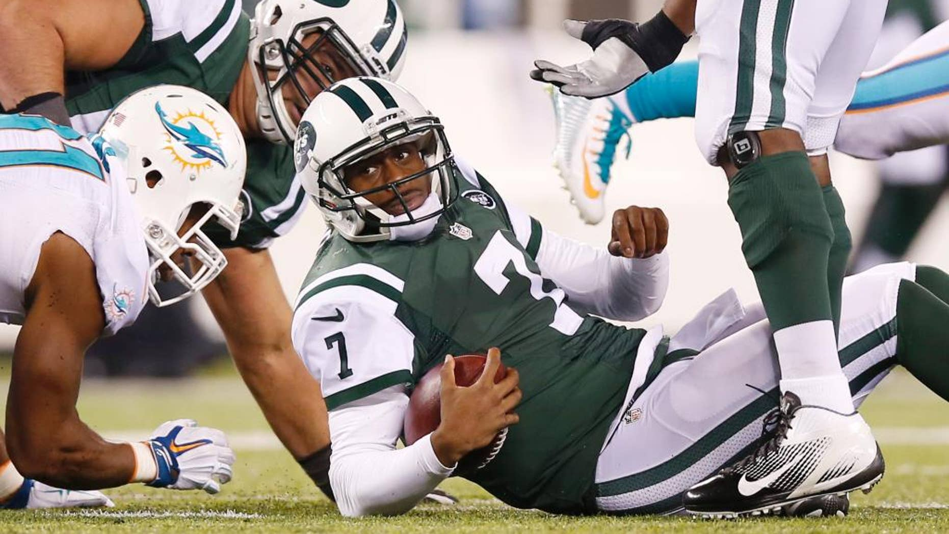 New York Jets quarterback Geno Smith (7) reacts after being sacked by the Miami Dolphins during the fourth quarter of an NFL football game, Monday, Dec. 1, 2014, in East Rutherford, N.J. (AP Photo/Kathy Willens)