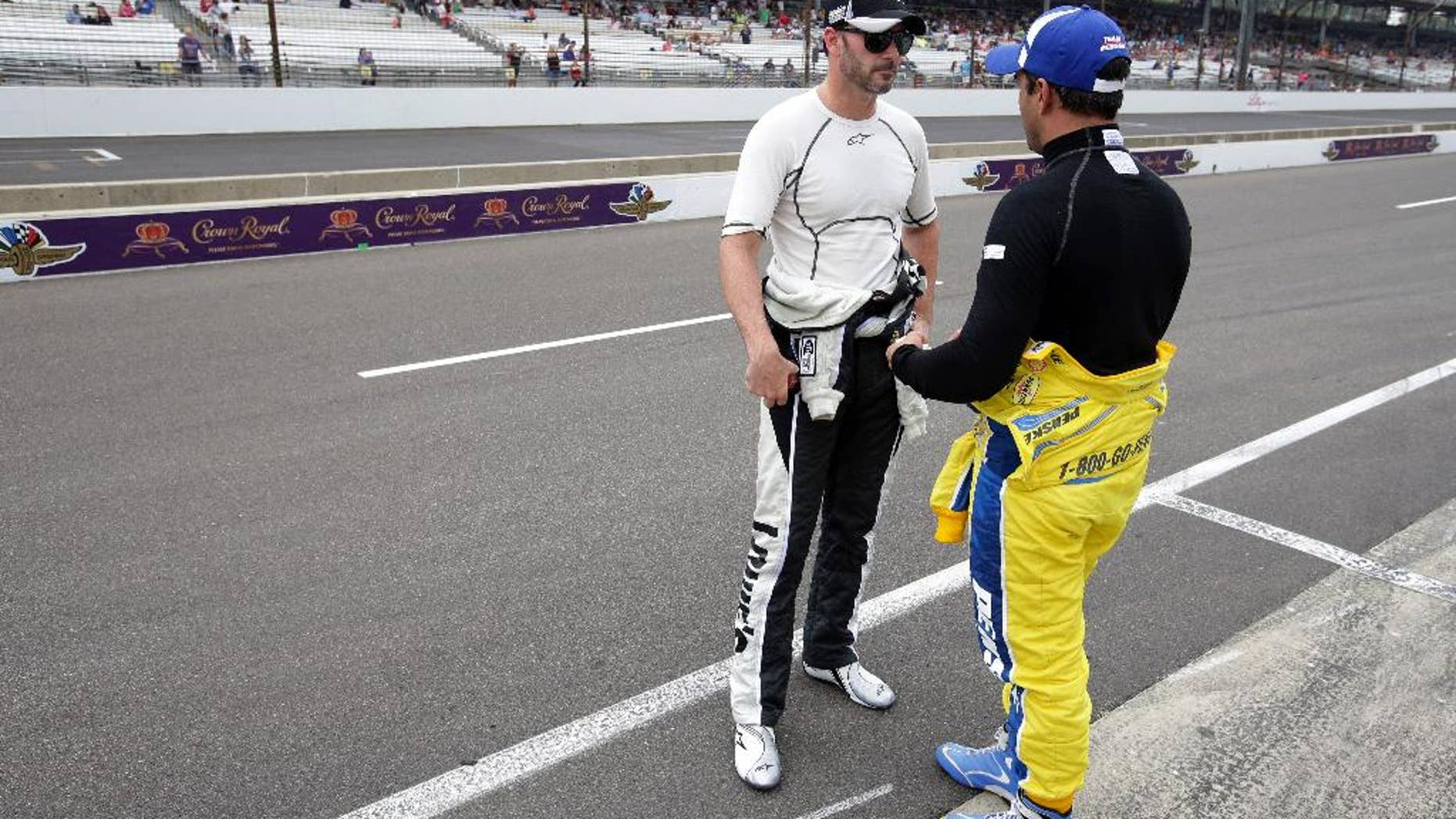Jimmie Johnson, left, talks with Juan Pablo Montoya after qualifications for the Brickyard 400 auto race at the Indianapolis Motor Speedway in Indianapolis, Saturday, July 26, 2014. (AP Photo/AJ Mast)