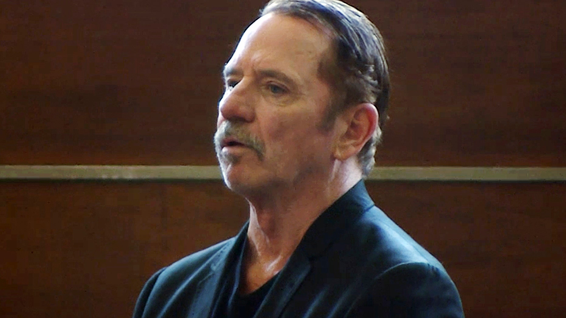 In this Aug. 3, 2017 file frame from video, actor Tom Wopat stands during arraignment in Waltham, Mass., on indecent assault and battery and drug possession charges.