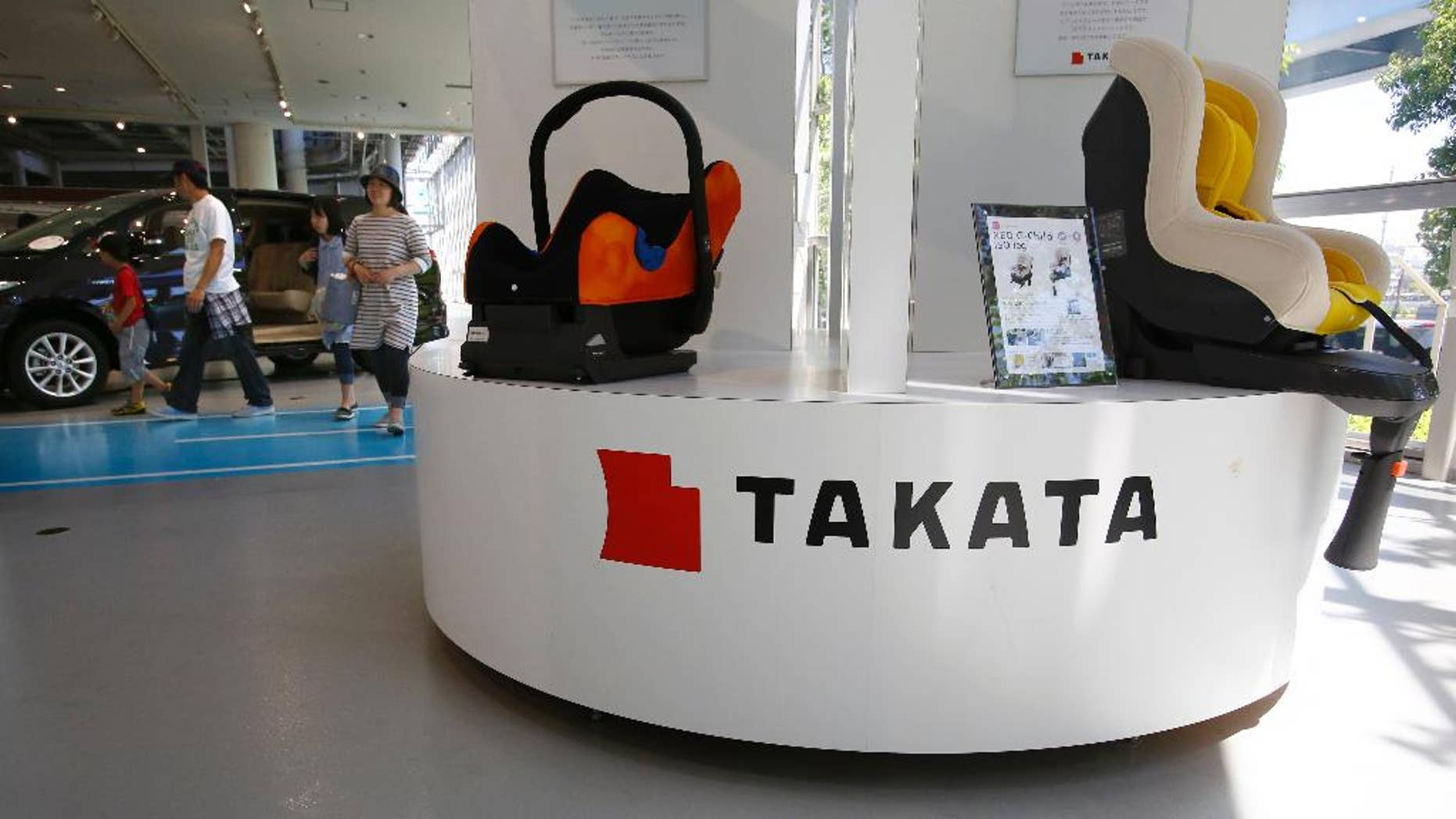 In this Wednesday, May 4, 2016 photo, a family walk by child seats manufactured by Japanese auto parts maker Takata Corp. at an automaker's showroom in Tokyo. Takata, which also makes seat belts, is expecting a loss instead of a profit for the fiscal year that ended in March because of ballooning costs from a massive global air-bag recall. Tokyo-based Takata, which is set to give its earnings report Wednesday, May 11, said Monday, May 9, it is projecting an annual net loss of 13 billion yen ($120 million). (AP Photo/Shizuo Kambayashi)