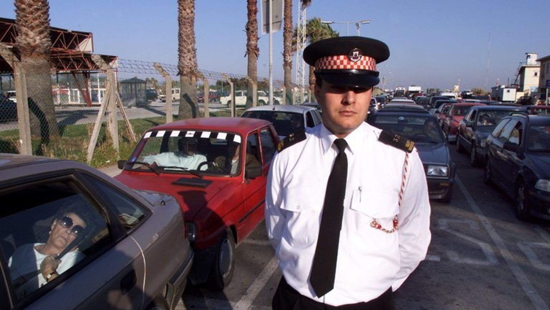 "File picture shows a policeman monitoring traffic as cars wait to cross from Gibraltar into Spain. The government said Sunday it had ""serious concerns"" after Gibraltar accused Madrid of deliberately creating delays to car traffic to and from the disputed British-held territory to Spain."