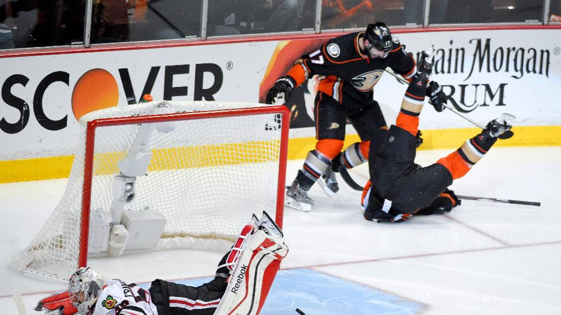 Anaheim Ducks left wing Matt Beleskey right, celebrates with Ryan Kesler after scoring the game winning goal past Chicago Blackhawks goalie Corey Crawford, left, during overtime in Game 5 of the Western Conference final of the NHL hockey Stanley Cup playoffs in Anaheim, Calif., on Monday, May 25, 2015. (AP Photo/Mark J. Terrill)