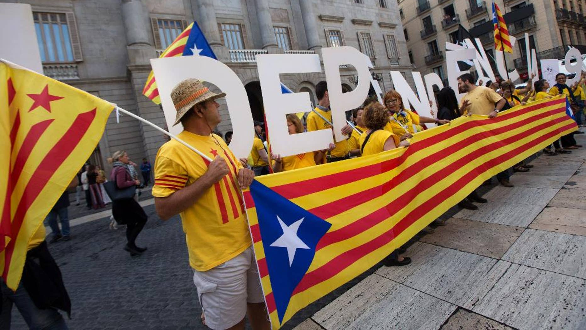 Pro independence supporters gather outside the Generalitat Palace, the main head office of the Government of Catalonia, as Catalonia's regional president Artur Mas, signs the decree to call the referendum in Catalonia in Barcelona, Spain, Saturday, Sept. 27, 2014.  The president of Spain's powerful northeastern region of Catalonia on Saturday formally called an independence referendum Nov. 9, the latest secession push in Europe and one of the most serious challenges to the Spanish state of recent years. (AP Photo/Jordi Borras)