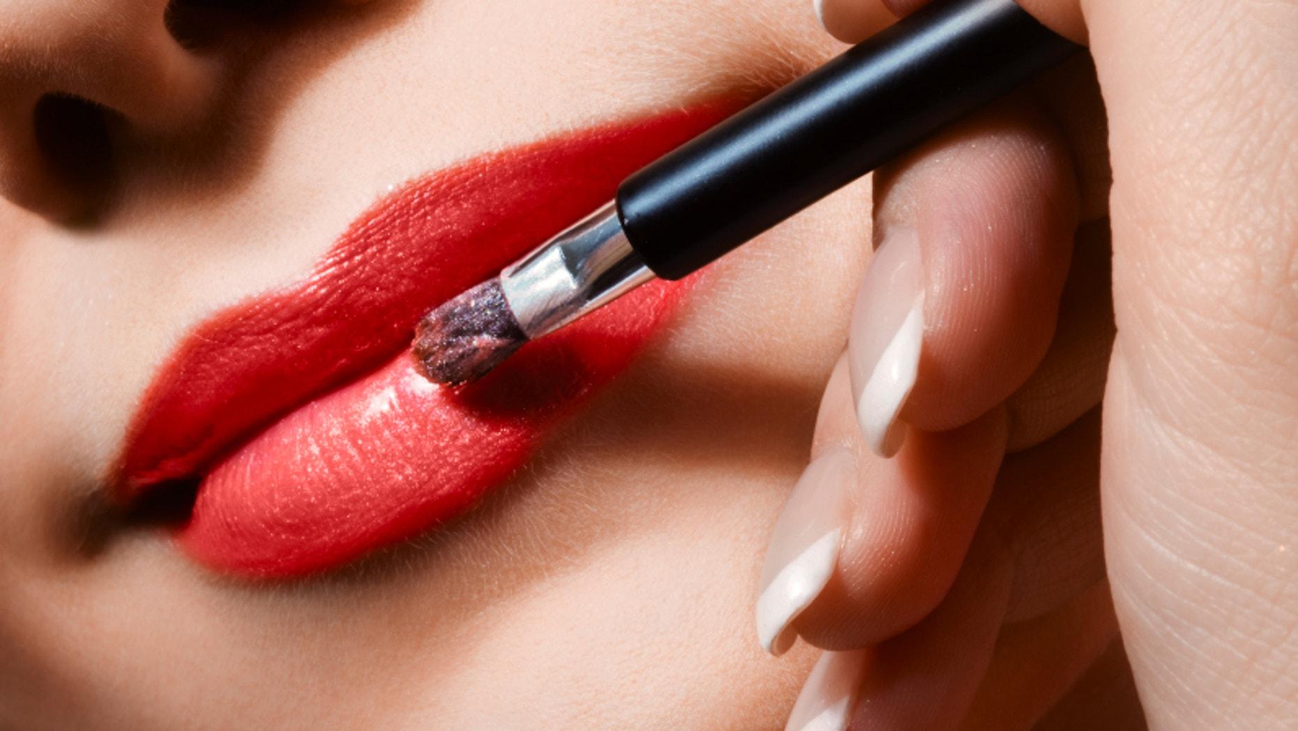 woman applying lipgloss on lips