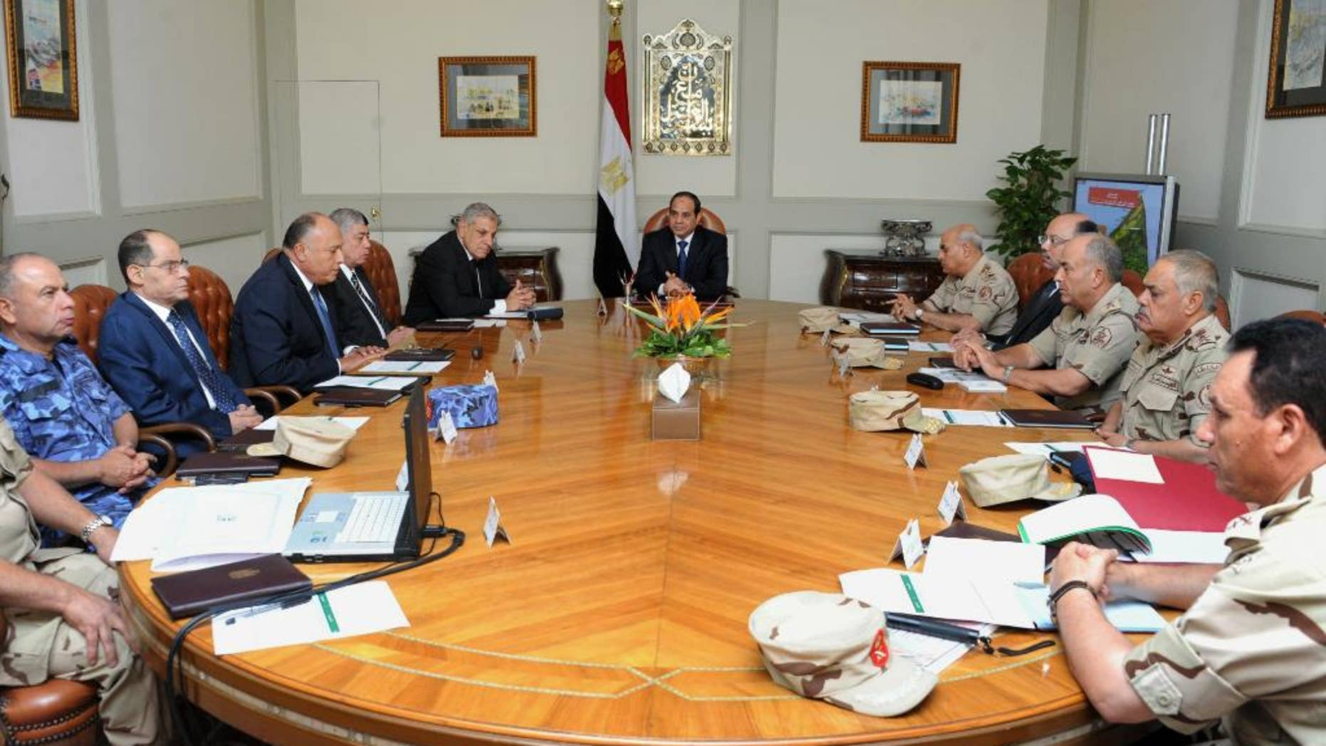 In this photo provided by Egypt's state news agency MENA, Egypt's President Abdel-Fattah el-Sissi, center, holds an emergency meeting of the National Defense Council with top officials after an attack in the Sinai Peninsula, in Cairo, Egypt, Friday, Oct. 24, 2014. The coordinated assault on an army checkpoint in the Sinai Peninsula killed 30 Egyptian troops on Friday, making it the deadliest single attack in decades on the military, which has been struggling to stem a wave of violence by Islamic extremists since the overthrow of Islamist President Mohammed Morsi. El-Sissi, the former defense minister and army chief who overthrew Morsi last year, declared a three-day mourning period. (AP Photo/MENA)