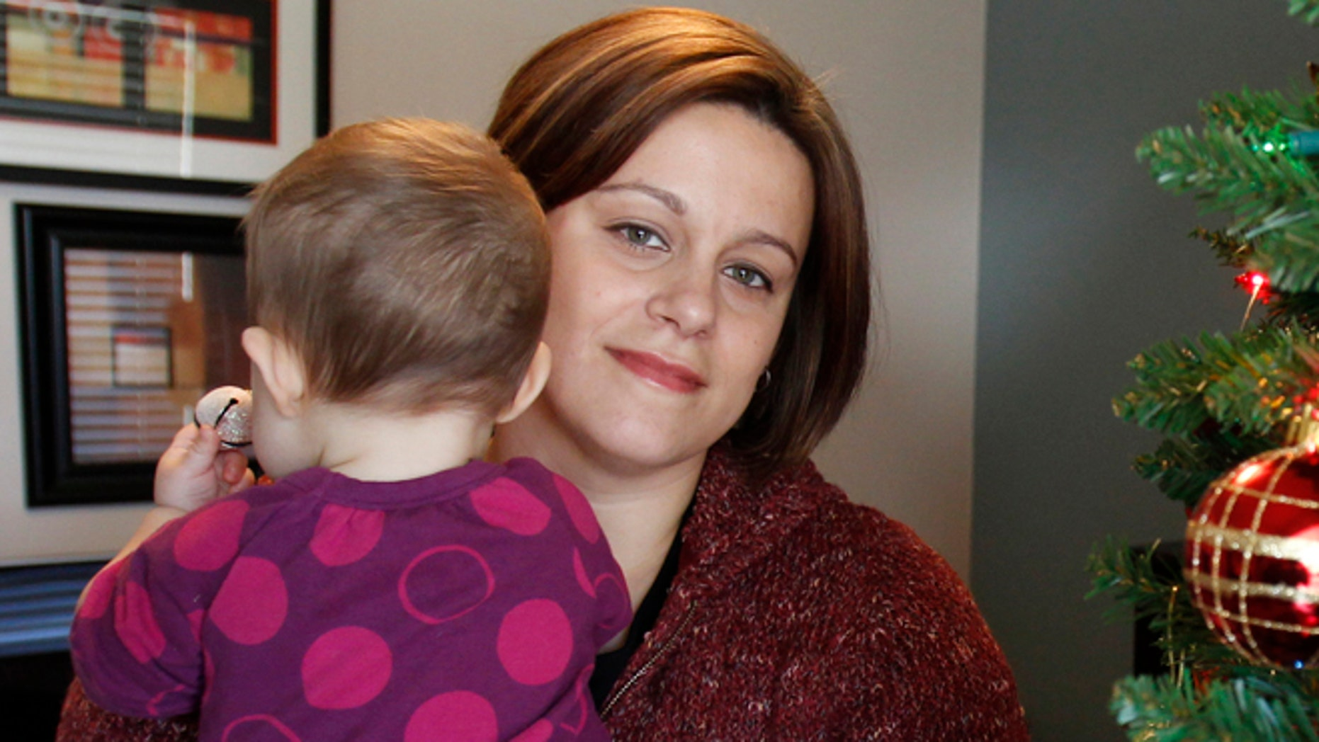 FILE - This photo made Dec. 8, 2011, in Withamsville, Ohio, shows teacher Christa Dias holding her 11-month-old daughter in her home.  (AP Photo/The Cincinnati Enquirer, Gary Landers, File)