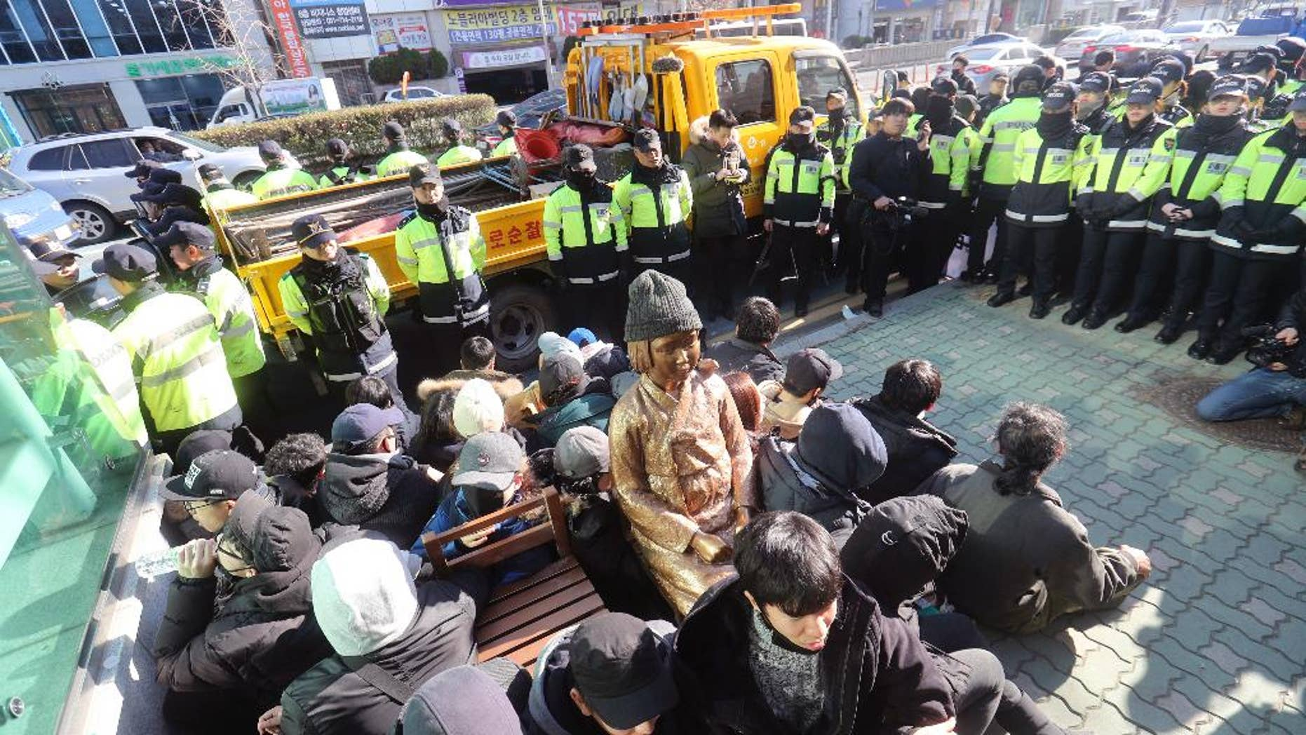 """In this Dec. 28, 2016, photo, members of civic groups sit around a comfort-woman statue after they set up in front of the Japanese consulate as police officers surround them in Busan, South Korea. Japan is recalling its ambassador to South Korea Friday, Jan. 6, 2017 in response to the placing of the statue. Many Koreans and other women in Asia were forced to work in brothels for the Japanese military during World War II in what was called the """"comfort-woman"""" system. (Kim Sun-ho/Yonhap via AP)"""