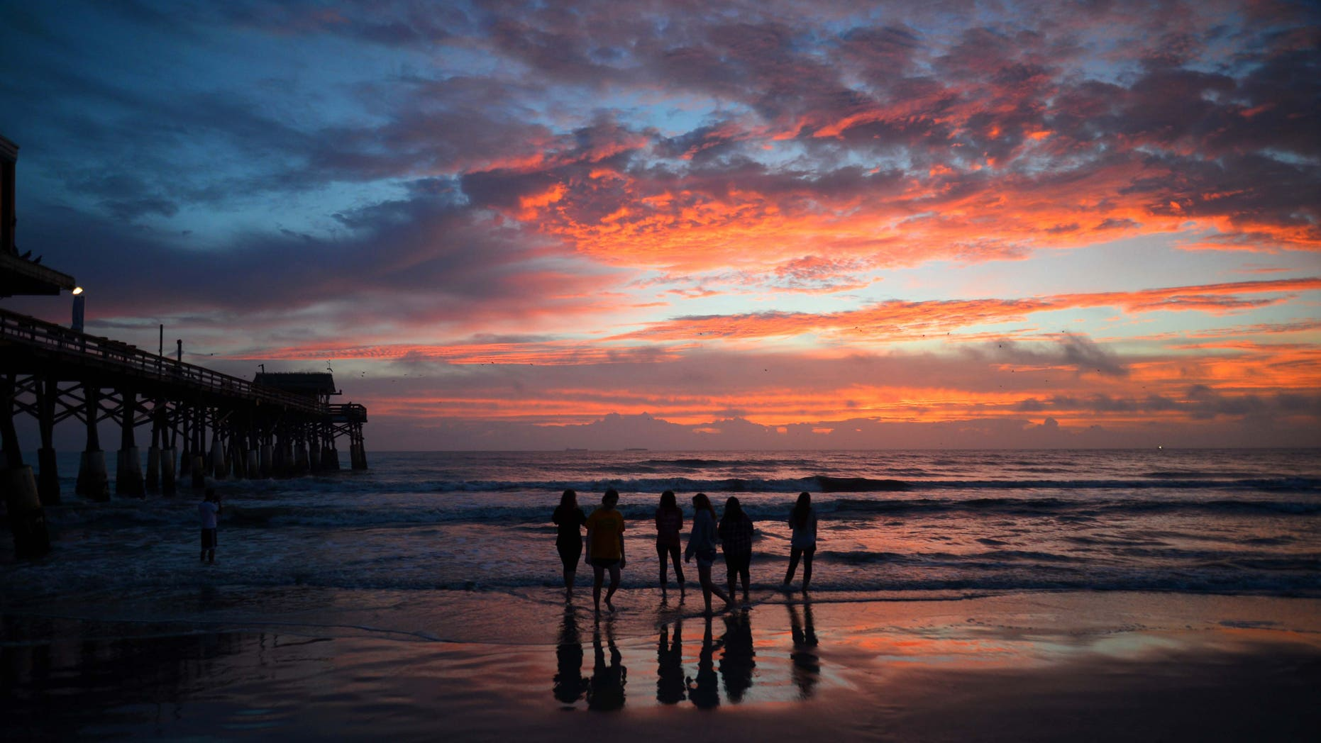 A group of Disney cast members watch the first sunrise of the new year by the Cocoa Beach Pier, Fla., Friday, Jan. 2016. (Malcolm Denemark/Florida Today via AP) MANDATORY CREDIT