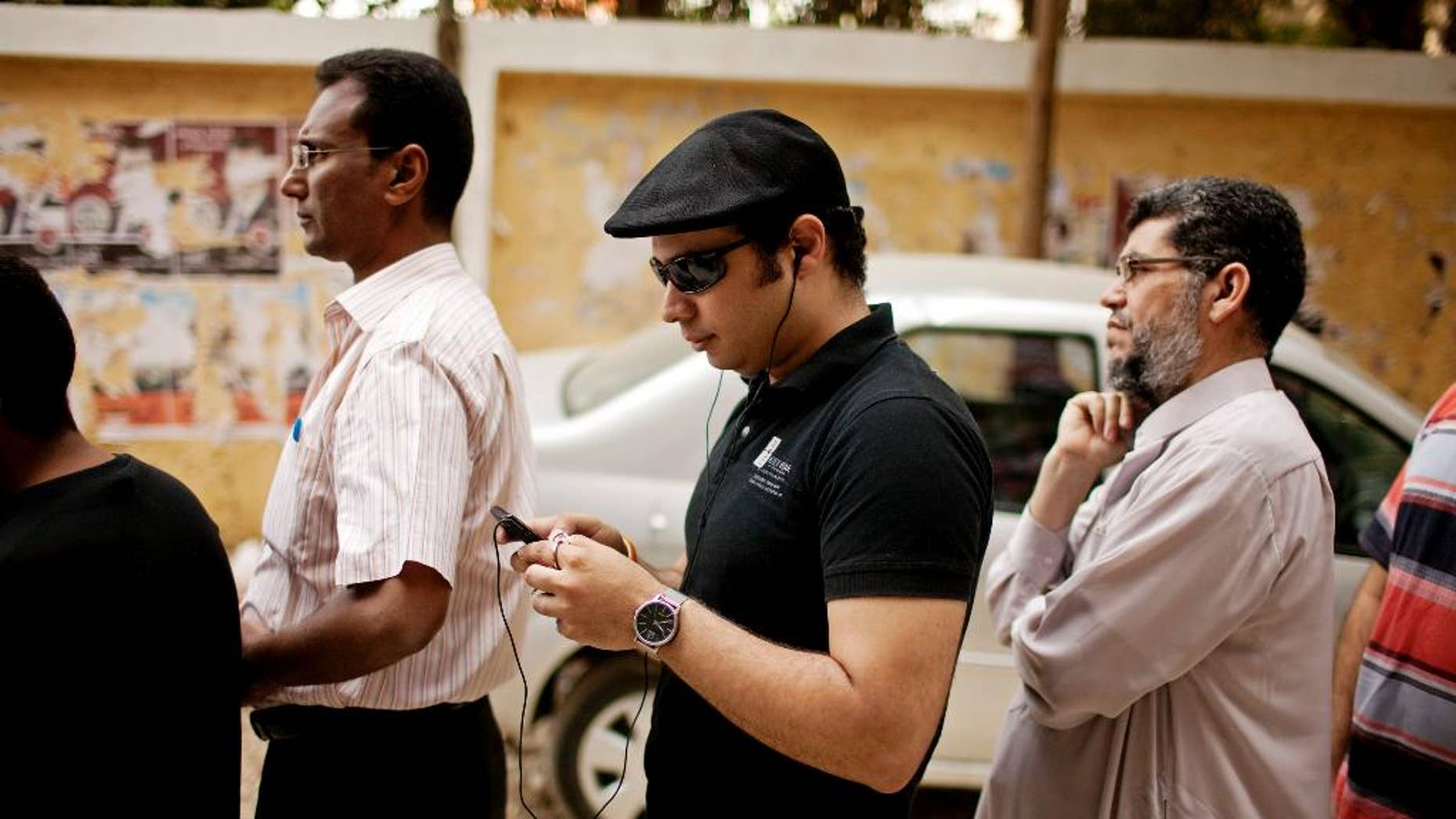 FILE -- In this May 23, 2012 file photo, Ahmed Maher, a co-founder of the April 6 Revolutionary Movement, waits in line to vote in presidential elections after 16 months of interim rule by the Supreme Council of Armed Forces, at a polling center in Cairo, Egypt. Maher, a leading Egyptian activist behind the 2011 uprising that toppled Hosni Mubarak has been released from prison after serving a three-year sentence for violating a ban on unauthorized protests. A lawyer for Maher, Tarek al-Awadi, said Maher will be under surveillance for the next three years as part of his sentence. (AP Photo/Pete Muller, File)