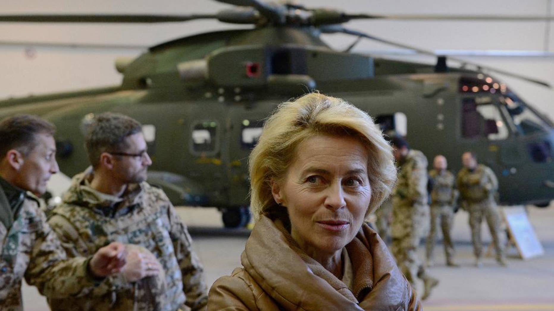 """FILE -  In this Dec. 13, 2014 file picture German Defense Minister Ursula von der Leyen, center, greets German helicopter pilots in a hangar at Camp Marmal in Mazar-i-Sharif, Afghanistan. Germany is affirming its growing role on the world stage in new security guidelines that mark another step away from its caution after World War II. A draft defense policy paper obtained by The Associated Press Tuesday  July 12, 2016 and due to be presented on Wednesday states that """"Germany is a globally highly connected country ... which has a responsibility to actively shape the global order.""""  (John MacDougall, Pool Photo via AP, file)"""