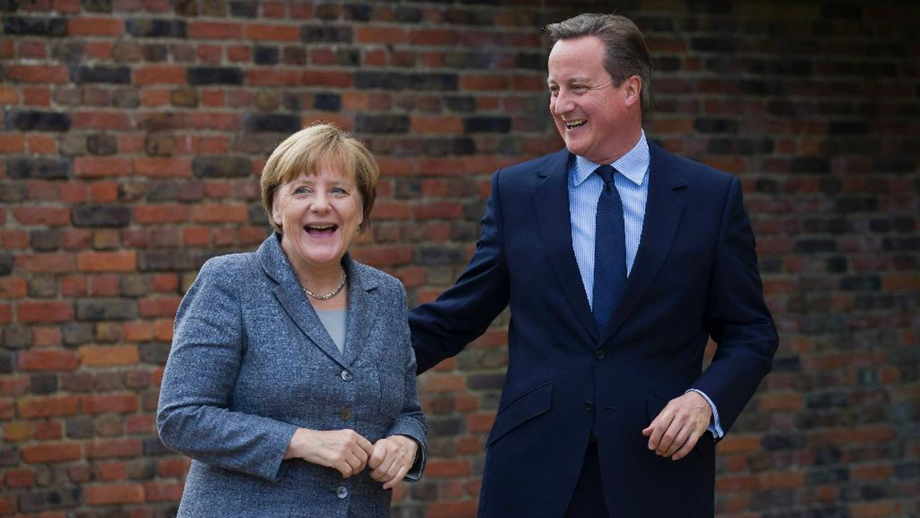 British Prime Minister David Cameron smiles as he talks with German Chancellor Angela Merkel during their meeting at Chequers, the prime minister's official country residence, near Ellesborough, northwest of London, Friday Oct. 9, 2015. (Justin Tallis/Pool via AP)