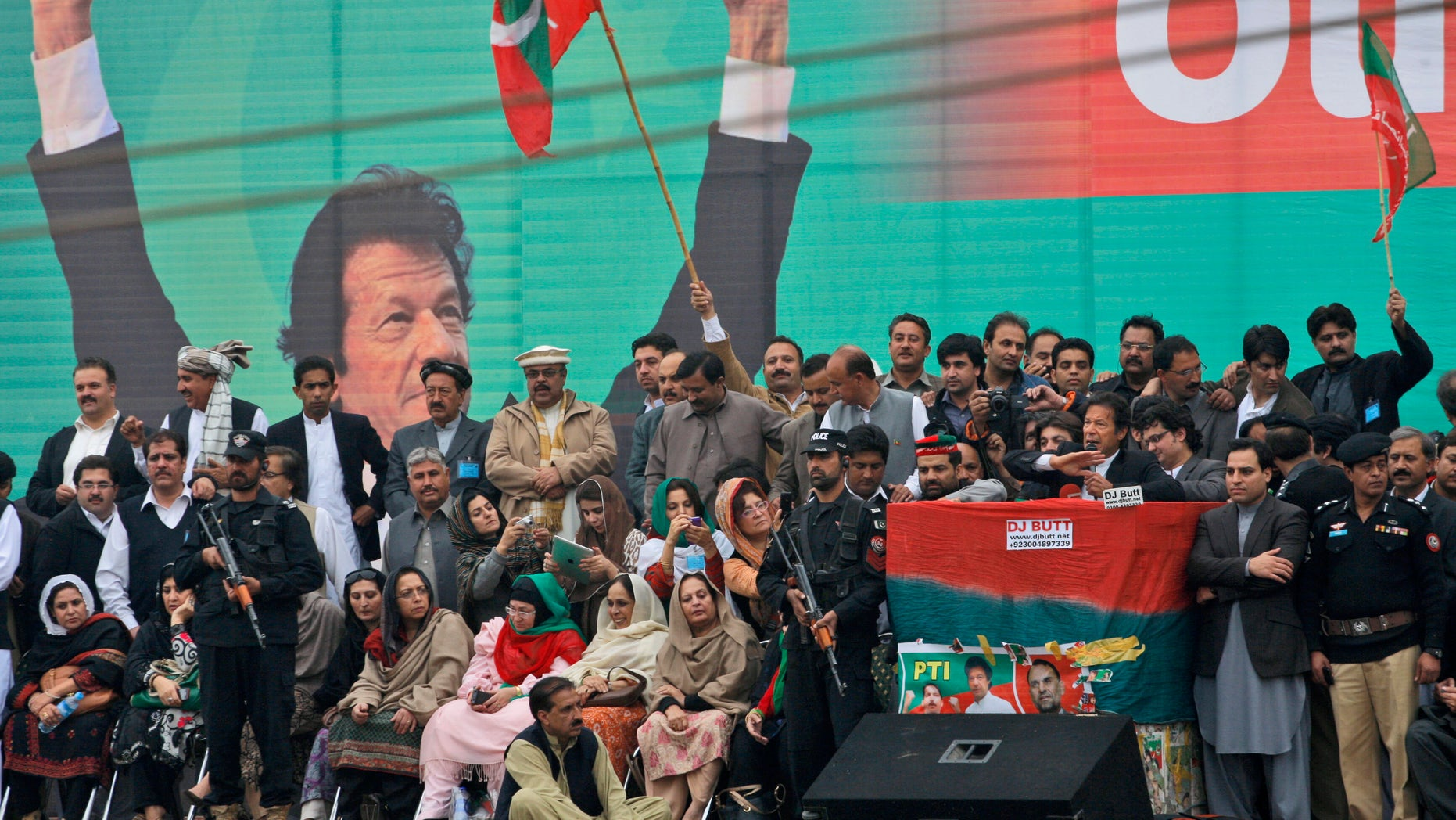 Nov. 23, 2013: Pakistan's cricketer-turned politician Imran Khan, leader of Pakistan Tehreek-e-Insaf party, with a microphone at center right, surrounded by security men and party members, delivers a speech to his supporters during a protest against U.S. drone strikes in Pakistan, in Peshawar, Pakistan. Thousands of people protesting U.S. drone strikes blocked a road in northwest Pakistan on Saturday used to truck NATO troop supplies and equipment in and out of Afghanistan, the latest sign of rising tension caused by the attacks.