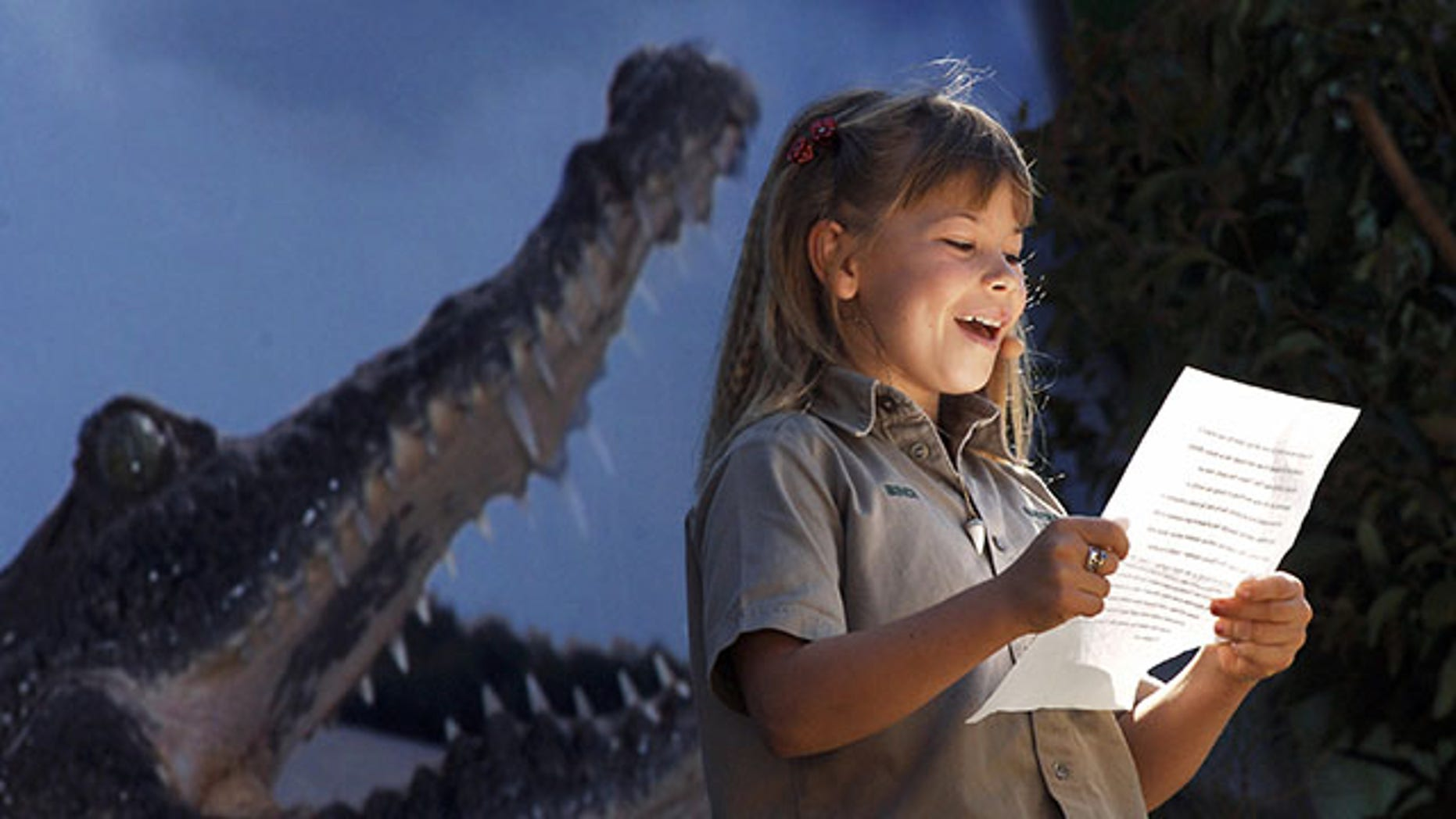 """BEERWAH, AUSTRALIA:  Eight-year-old Bindi Irwin, daughter of Australian environmentalist and television personality Steve Irwin, reads a tribute to her father during a memorial service for her husband at Australia Zoo in Beerwah, in the Australian state of Queensland, 20 September 2006. Family, friends, fans and movie stars bade a final farewell to """"Crocodile Hunter"""" Steve Irwin in a high-energy memorial service fuelled by laughter, tears and music. Irwin, known as the """"Crocodile Hunter"""", was killed 04 September by a stingray barb during a diving expedition.  AFP PHOTO/POOL/DAVE HUNT  (Photo credit should read DAVE HUNT/AFP/Getty Images)"""
