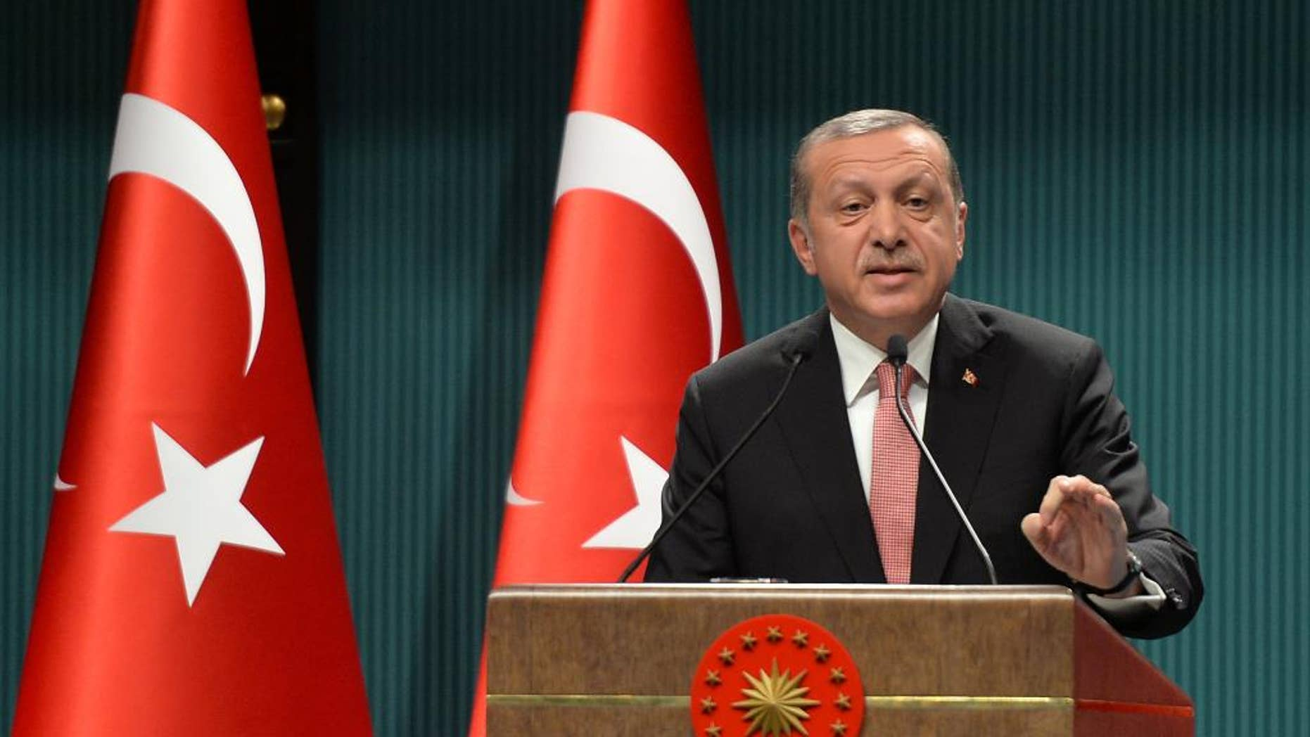 FILE - This is a Wednesday, July 20, 2016   file photo of Turkey's President Recep Tayyip Erdogan as he speaks after an emergency meeting of the government in Ankara, Turkey. Erdogan hinted on Thursday  Sept. 29, 2016 that the three-month state of emergency declared following the failed July 15 coup could be extended to over a year, a day after the national security council recommended it be extended for another three months.  (AP Photo/File)