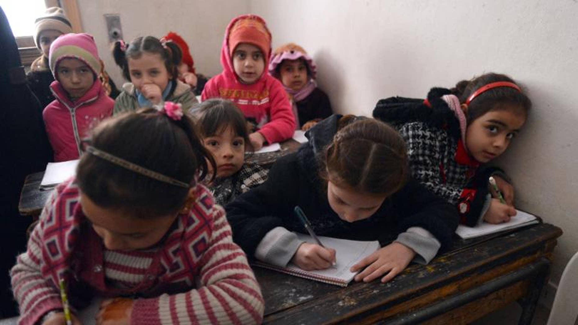 Syrian children attend a class at a school in the Kadi Askar area in the Syria's northern city of Aleppo on February 9, 2013.
