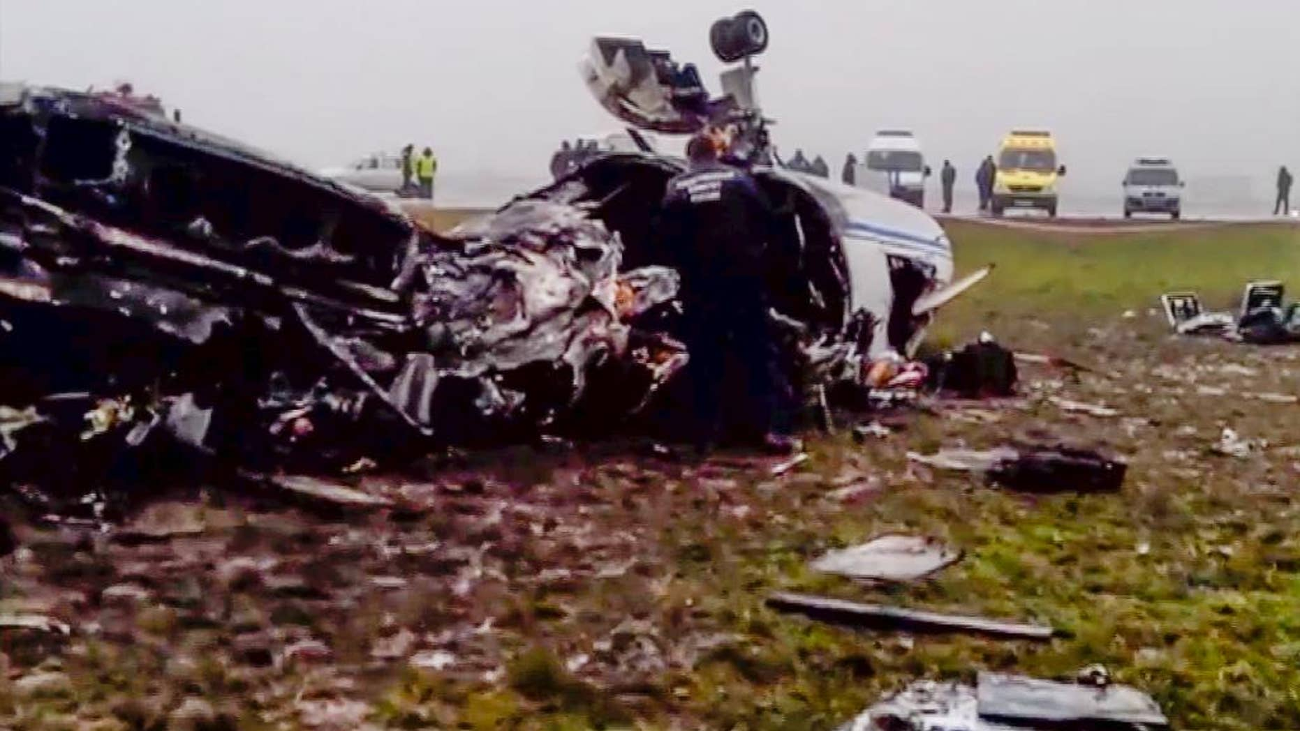 In this image made from video provided by Russian State Television Rossiya, investigators works at the wreckage of a private jet which collided with a snowplow at Vnukovo airport in Moscow, Tuesday, Oct. 21, 2014. The head of French oil giant Total SA and three French crew members were killed at Vnukovo airport when a corporate jet, the French-made Dassault Falcon 50, collided with a snowplow, Russian investigators said Tuesday. (AP Photo) TV OUT