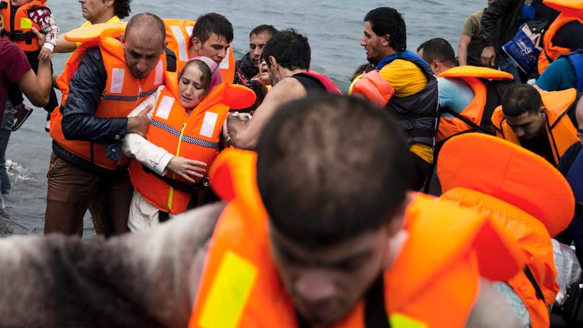 Syrian refugees arrive on the shores of the Greek island of Lesbos after crossing the Aegean Sea from Turkey on a inflatable dinghy , Tuesday,  Sept. 22, 2015. More than 260,000 asylum-seekers have arrived in Greece so far this year, most reaching the country's eastern islands on flimsy rafts or boats from the nearby Turkish coast. (AP Photo/Petros Giannakouris)