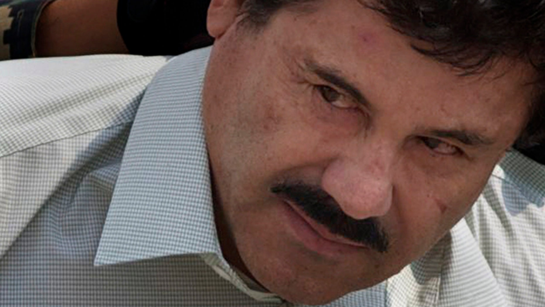 FILE - In this Feb. 22, 2014 file photo, Joaquin 'El Chapo' Guzman is escorted to a helicopter in handcuffs by Mexican Navy marines at a navy hanger in Mexico City. (AP Photo/Eduardo Verdugo, File)