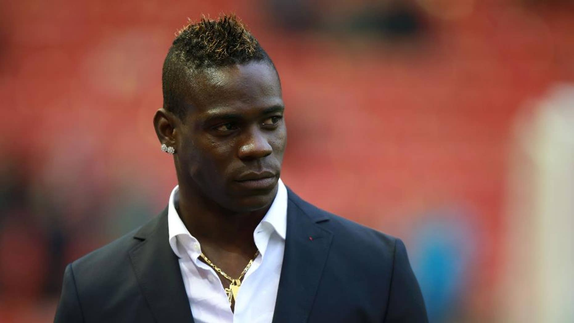 Liverpool's Mario Balotelli stands at the side of the pitch prior to the English Premier League soccer match between Liverpool and Stoke City at Anfield, Liverpool, England, Saturday Nov. 29, 2014. (AP Photo/PA, Peter Byrne) UNITED KINGDOM OUT