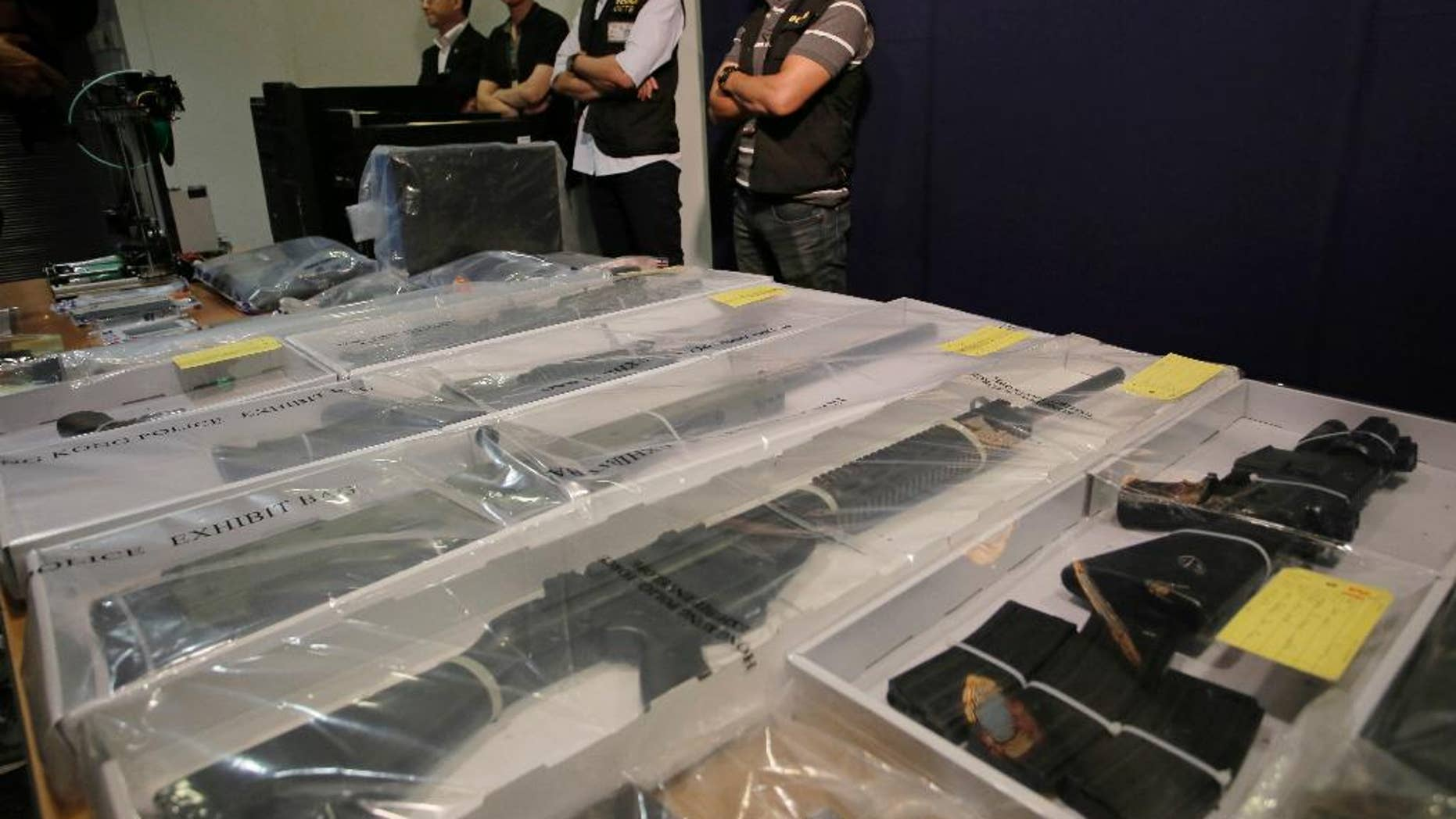 Plain clothed policemen stand guard in front of some air rifles and other evidences during a press conference in Hong Kong, Monday, June 15, 2015. Hong Kong police say they have arrested nine people, members of a local radical group and seized materials for making explosives. (AP Photo/Vincent Yu)