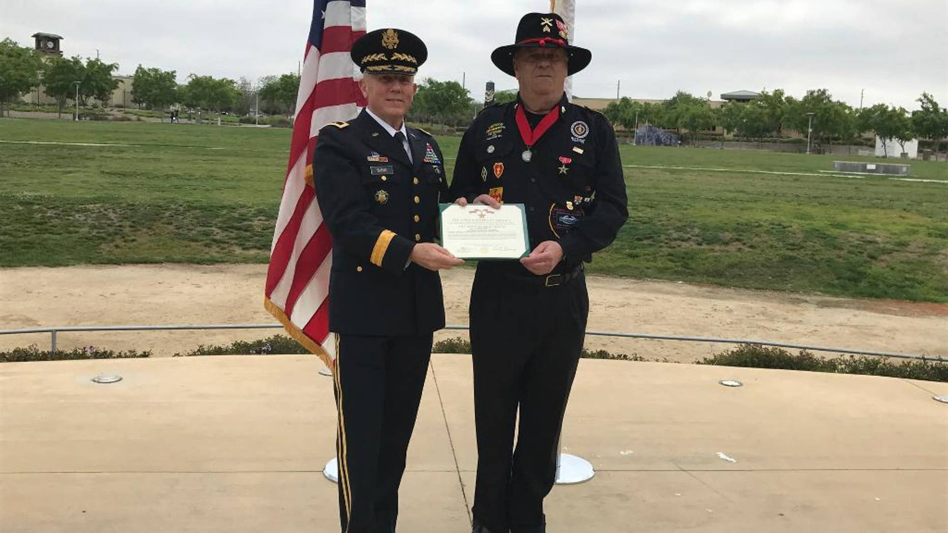 In this Monday, March 20, 2017, photo provided by the California Army National Guard, former Army Maj. Gen. Juilian Burns, left, presents retired U.S. Army Sgt. Joseph Engles with the Bronze Star during a ceremony in his hometown of Murrieta, Calif. Engles received the honor for gallantry in the face of the enemy during the Battle of Suoi Tre, Vietnam in March 1967. (Capt. Will Martin/California Army National Guard via AP)