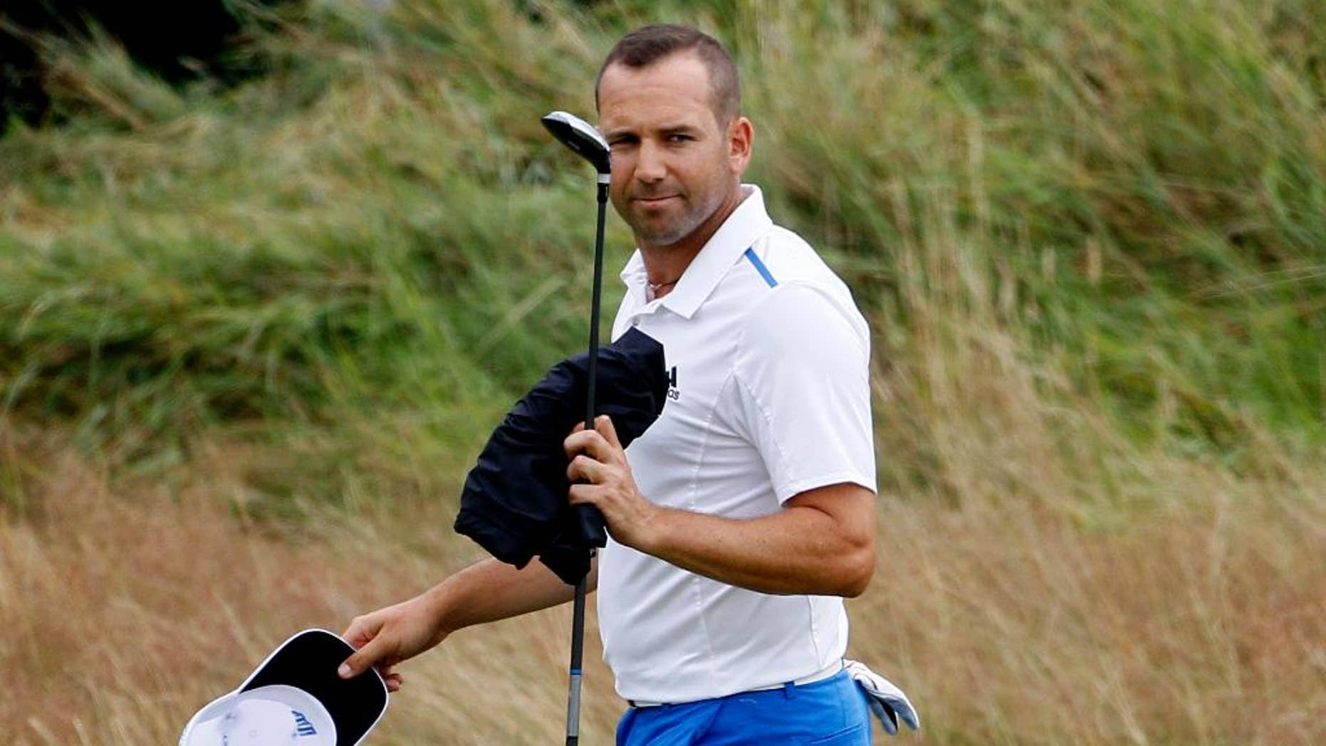 Sergio Garcia of Spain walks along the 18th fairway during the third day of the British Open Golf championship at the Royal Liverpool golf club, Hoylake, England, Saturday July 19, 2014. (AP Photo/Peter Morrison)