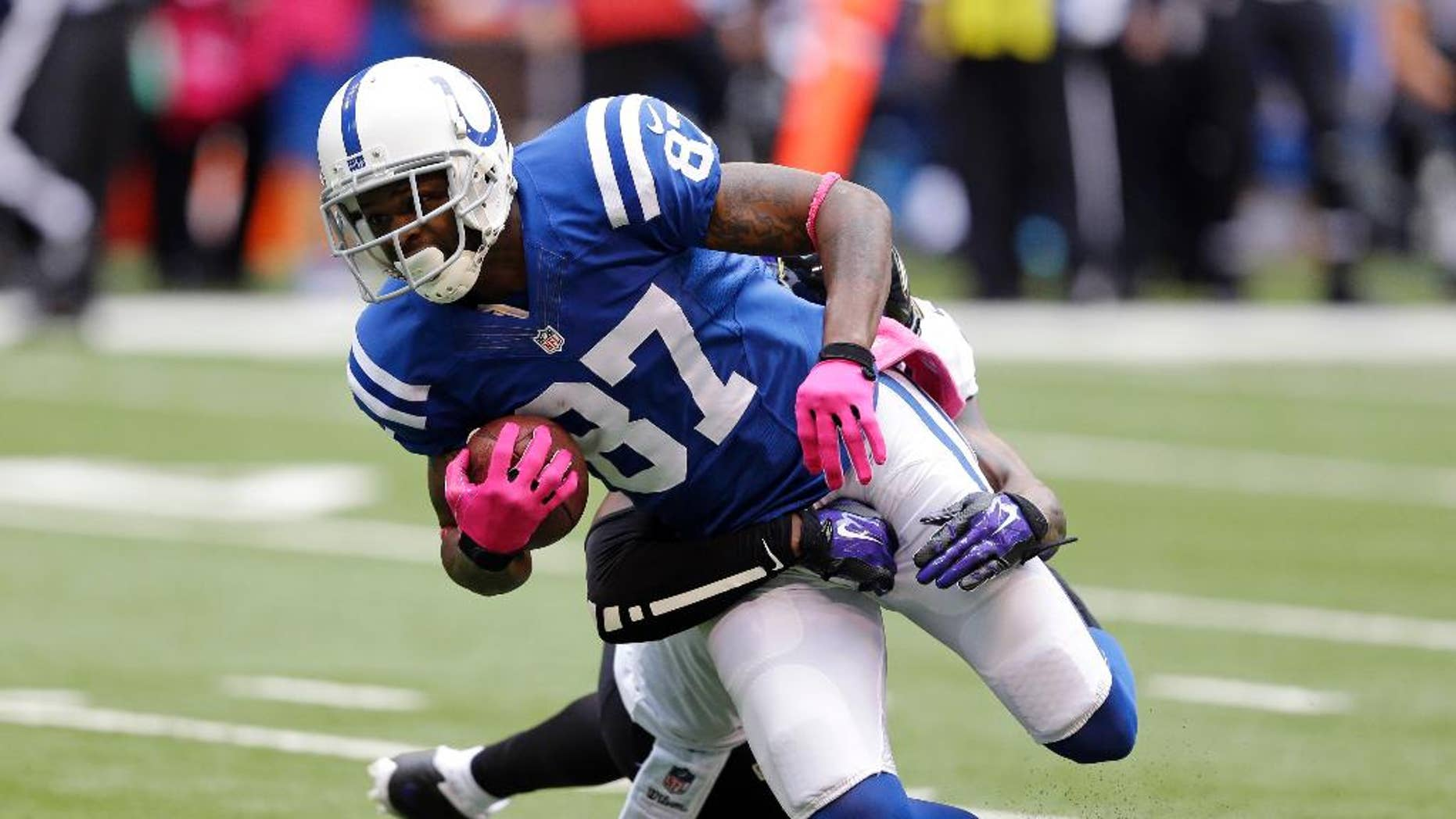 Indianapolis Colts wide receiver Reggie Wayne (87) is tackled by Baltimore Ravens free safety Darian Stewart after a first down during the first half of an NFL football game in Indianapolis, Sunday, Oct. 5, 2014. (AP Photo/Michael Conroy)