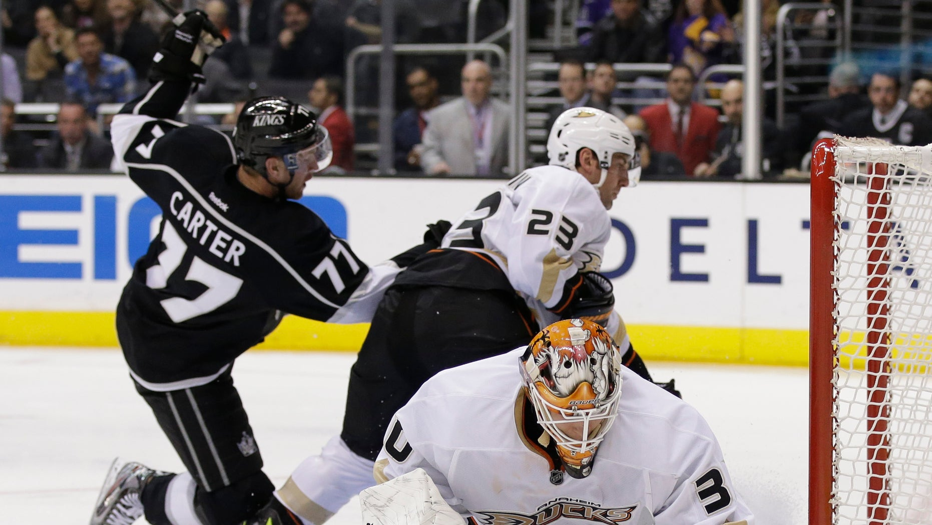 Anaheim Ducks goalie Viktor Fasth, right, blocks a shot by Los Angeles Kings center Jeff Carter(37) with the help of Francois Beauchemin(22) during the second period of an NHL hockey game in Los Angeles, Monday, Feb. 25, 2013. (AP Photo/Chris Carlson)