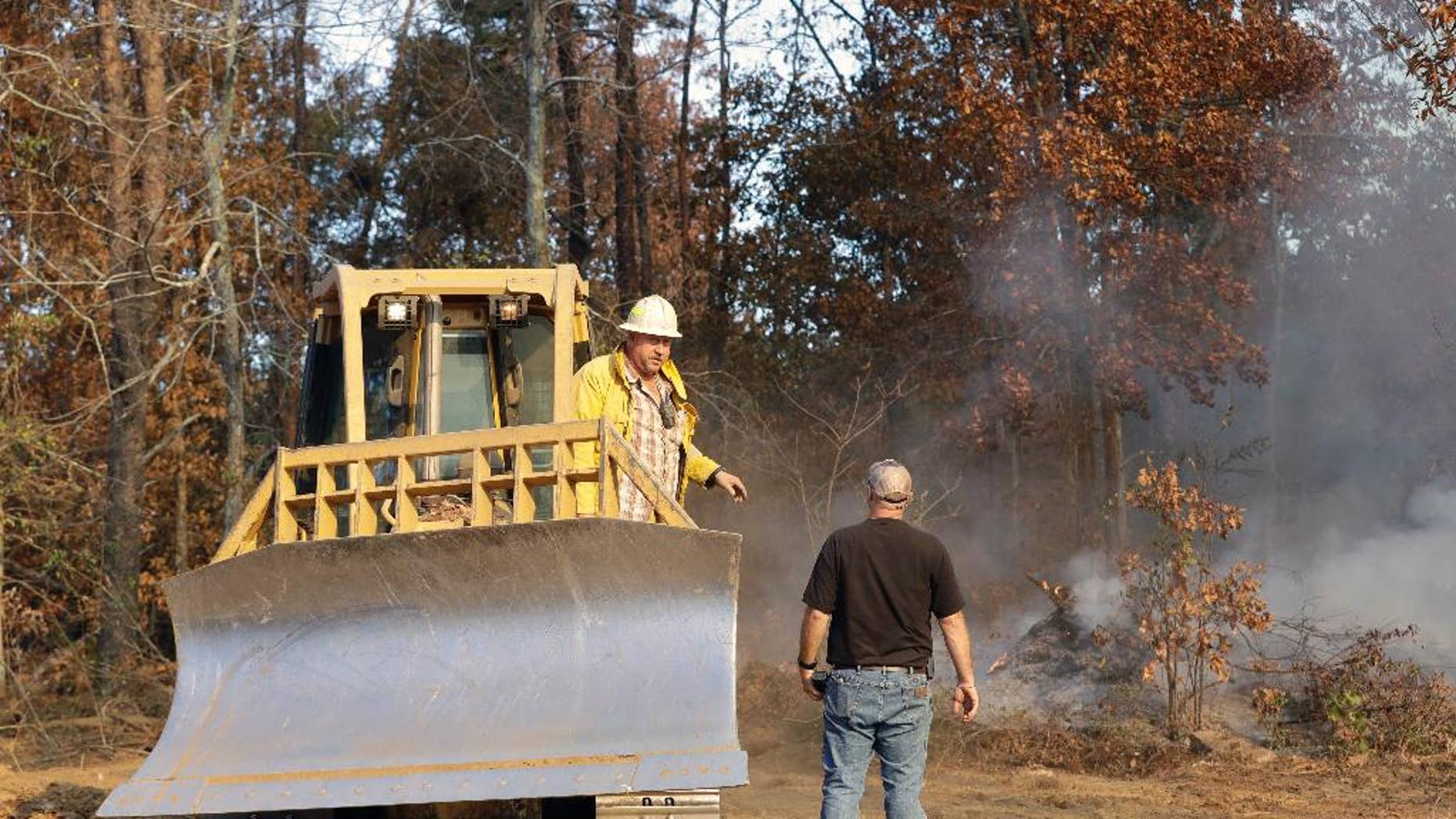 Bulldozer operator Jody McDonald, left, talks with Assistant Chief Dusten Woodard, right, of the Mowbray Volunteer Fire Depart, as McDonald cuts a firebreak to fight a wildfire Thursday, Nov. 10, 2016, in Soddy-Daisy, Tenn. Federal authorities say warmer-than-average temperatures and no rainfall are deepening a drought that's sparking forest fires across the Southeastern U.S. (AP Photo/Mark Humphrey)