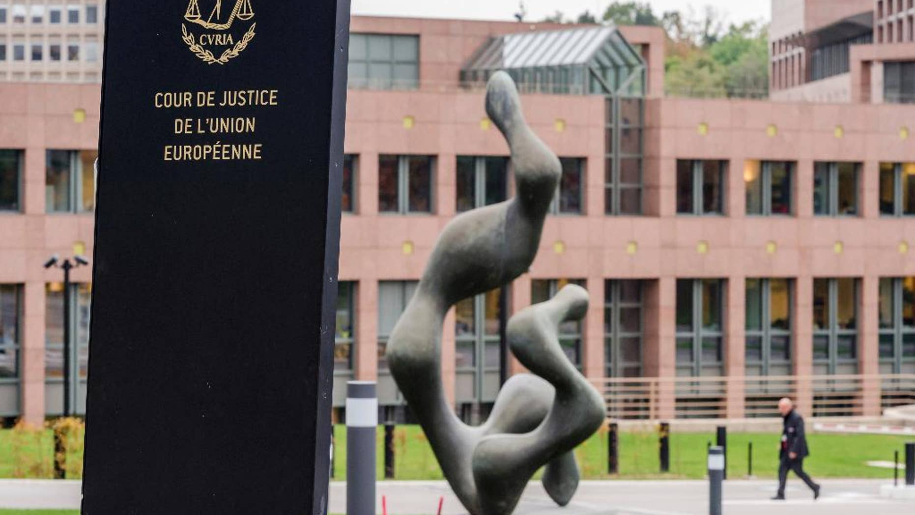 FILE - In this  Oct. 5, 2015 file photo, a man walks by the European Court of Justice in Luxembourg. The European Court of Justice ruled on Tuesday, Jan. 31, 2017, that an asylum request can be rejected if the person seeking protection has links to a terrorist group. (AP Photo/Geert Vanden Wijngaert, File)